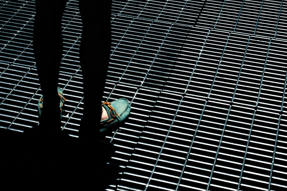 person standing on gray steel grills