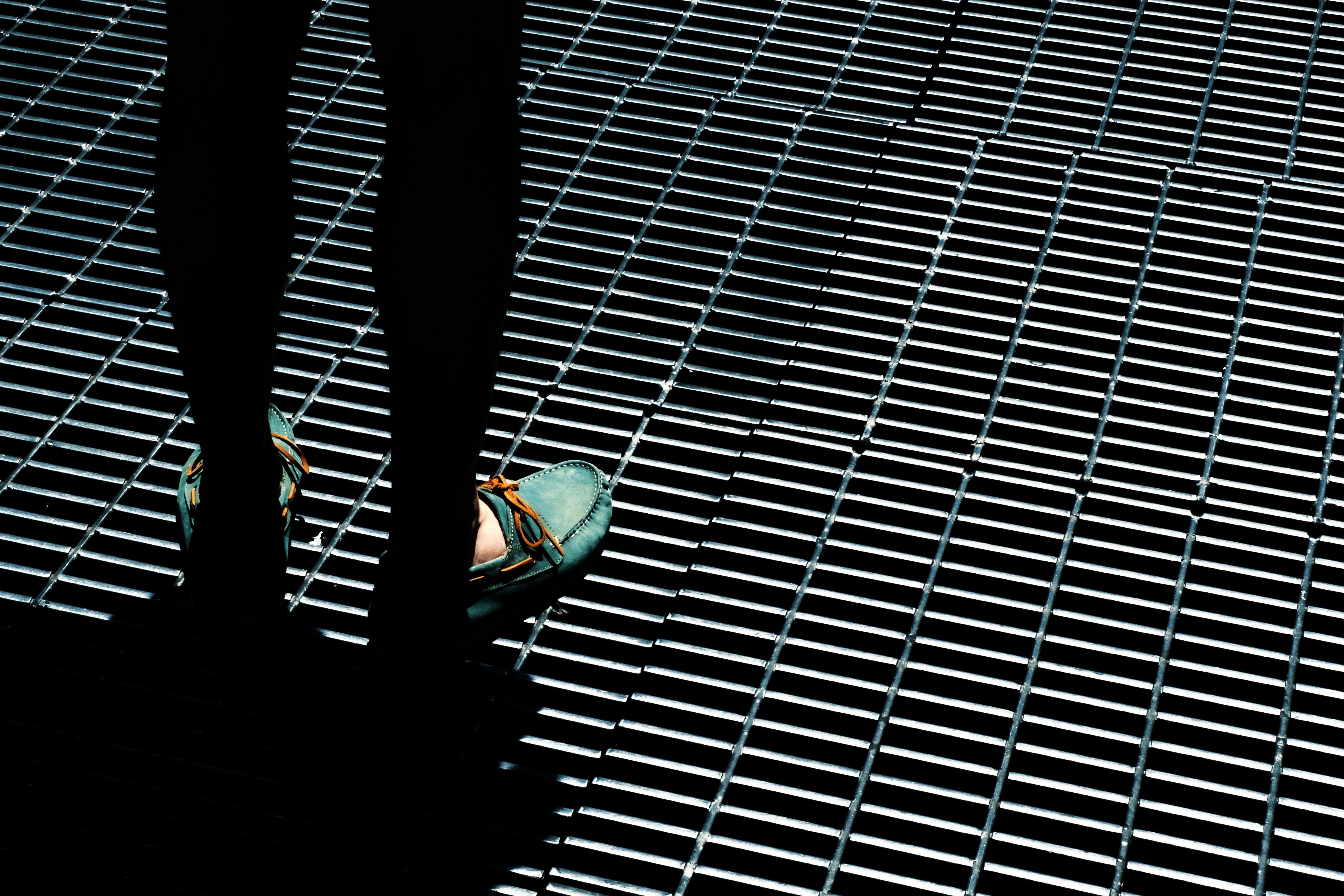 Silhouette of the legs of a person standing on the metal drain grates wearing turquoise loafers.