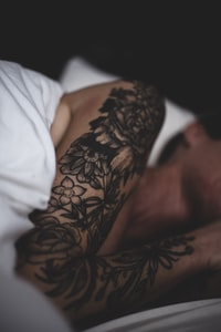 selective focus photo of black floral arm tattoo