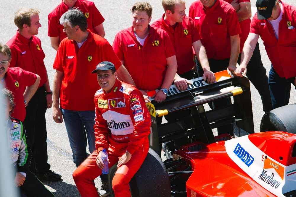 man sitting on black and red F1 car