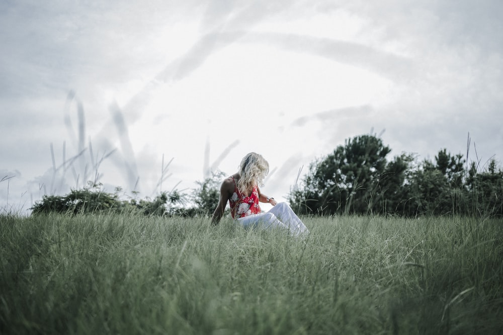 woman in red shirt and white pants sitting on green grass field