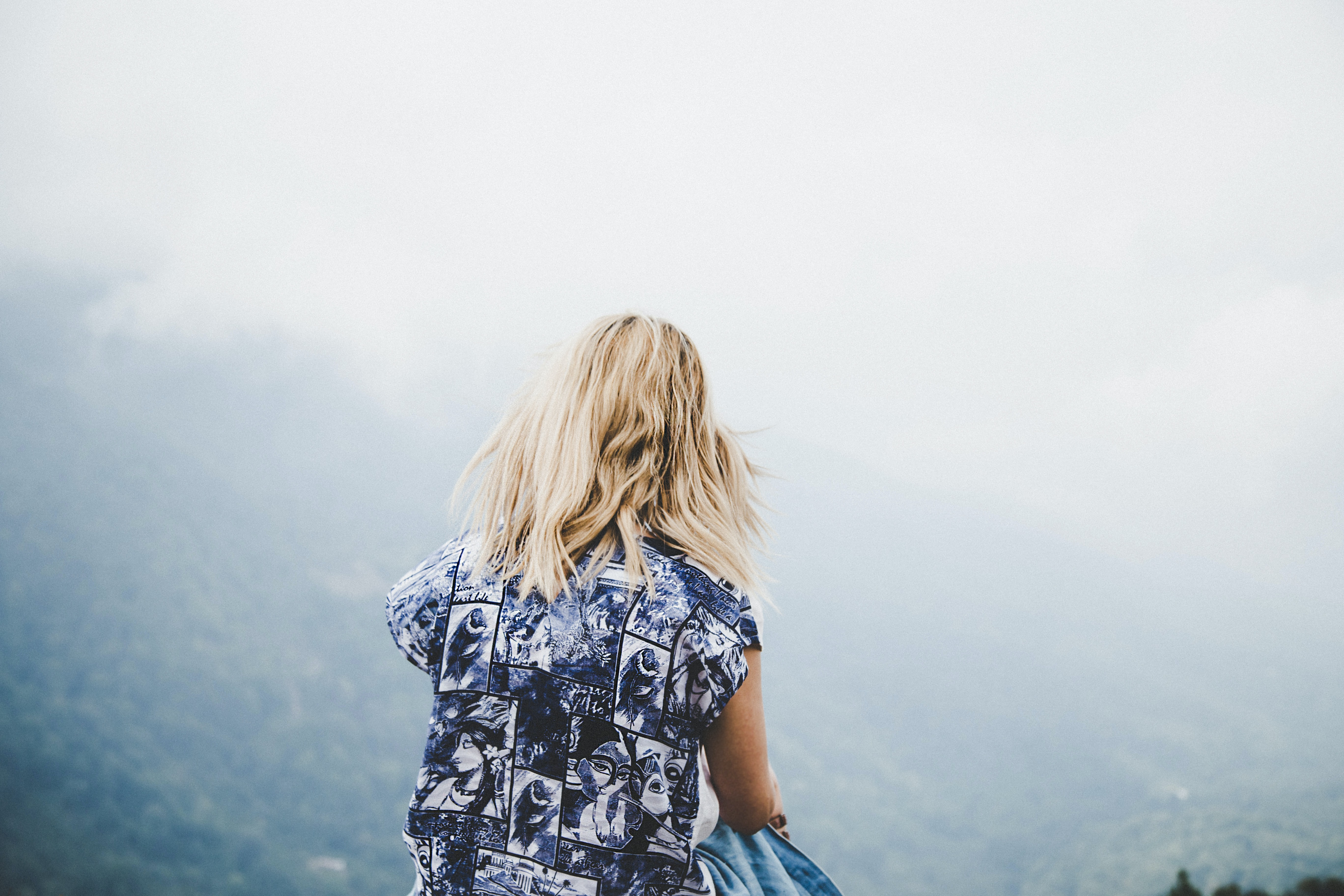 Woman with blonde hair and blue dress standing on a hill, looking at fog covering mountain