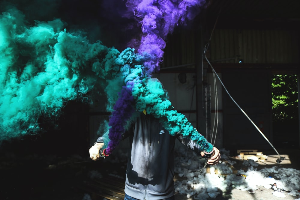 person holding purple and green smoker bottle during daytime