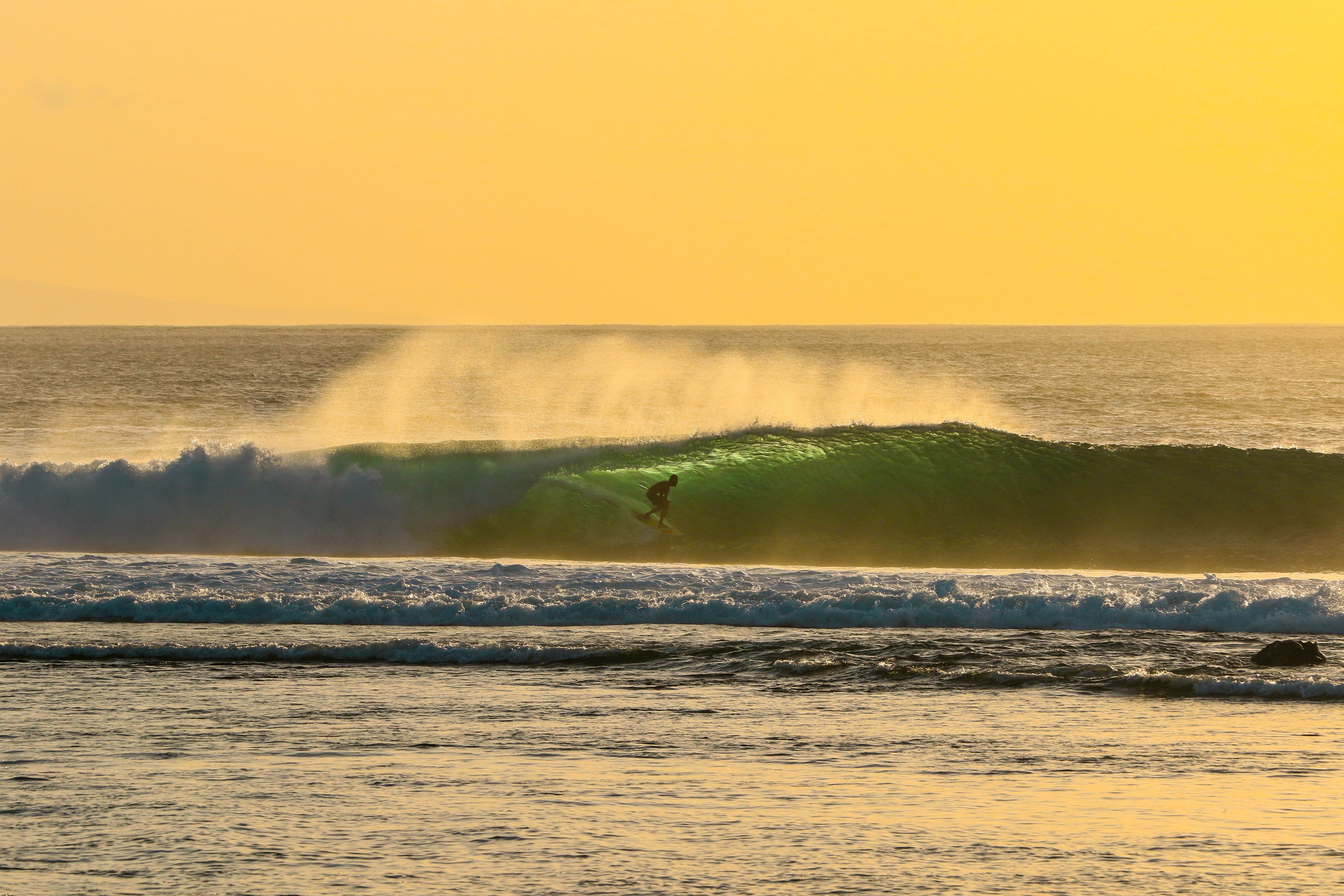A lone surfer riding a wave against a bright yellow sky in Lombok