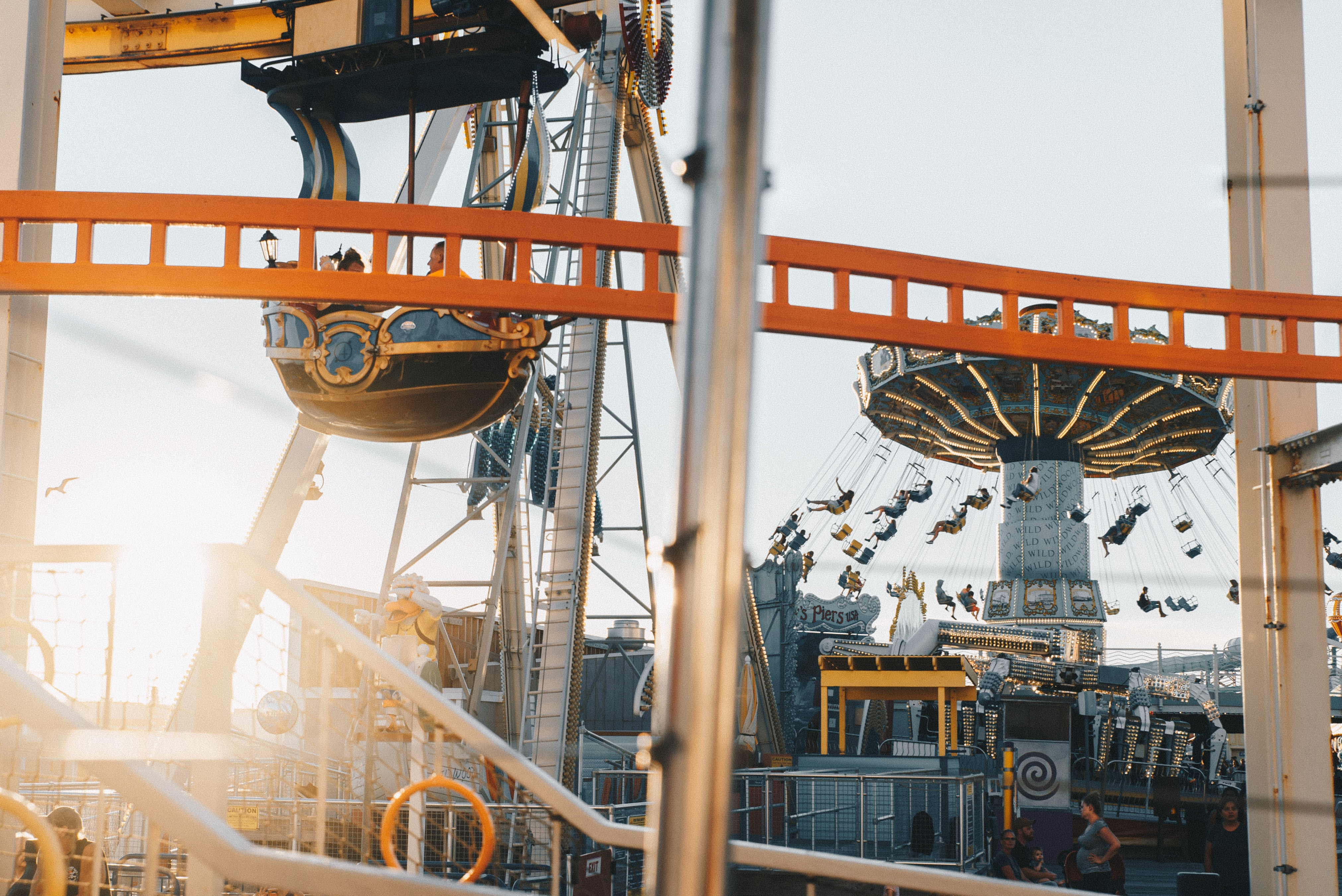 People at Morey's Piers & Beachfront Water Parks enjoying the swing ride and Ferris Wheel at sunset