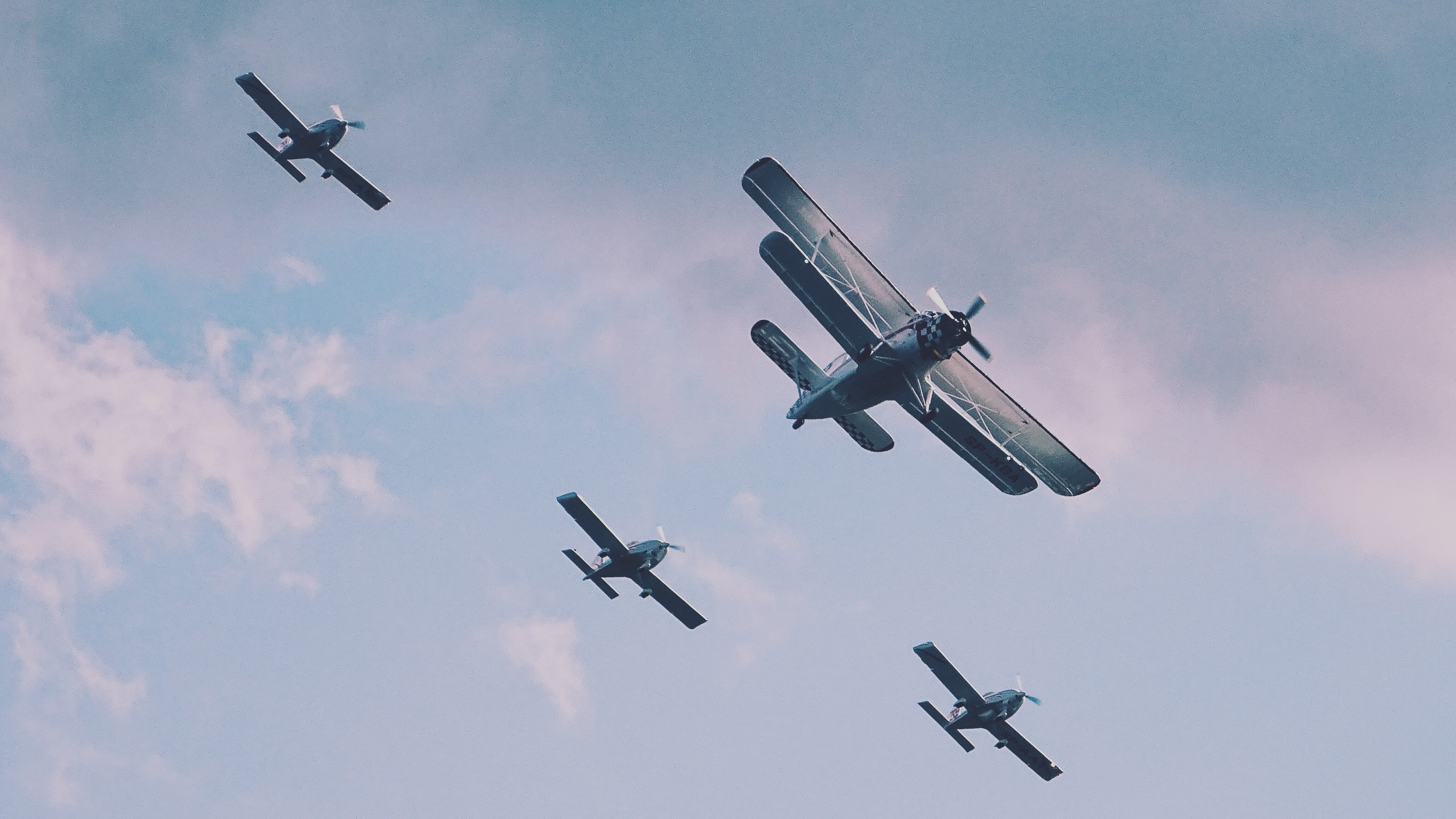 A fleet of vintage planes flying at an airshow