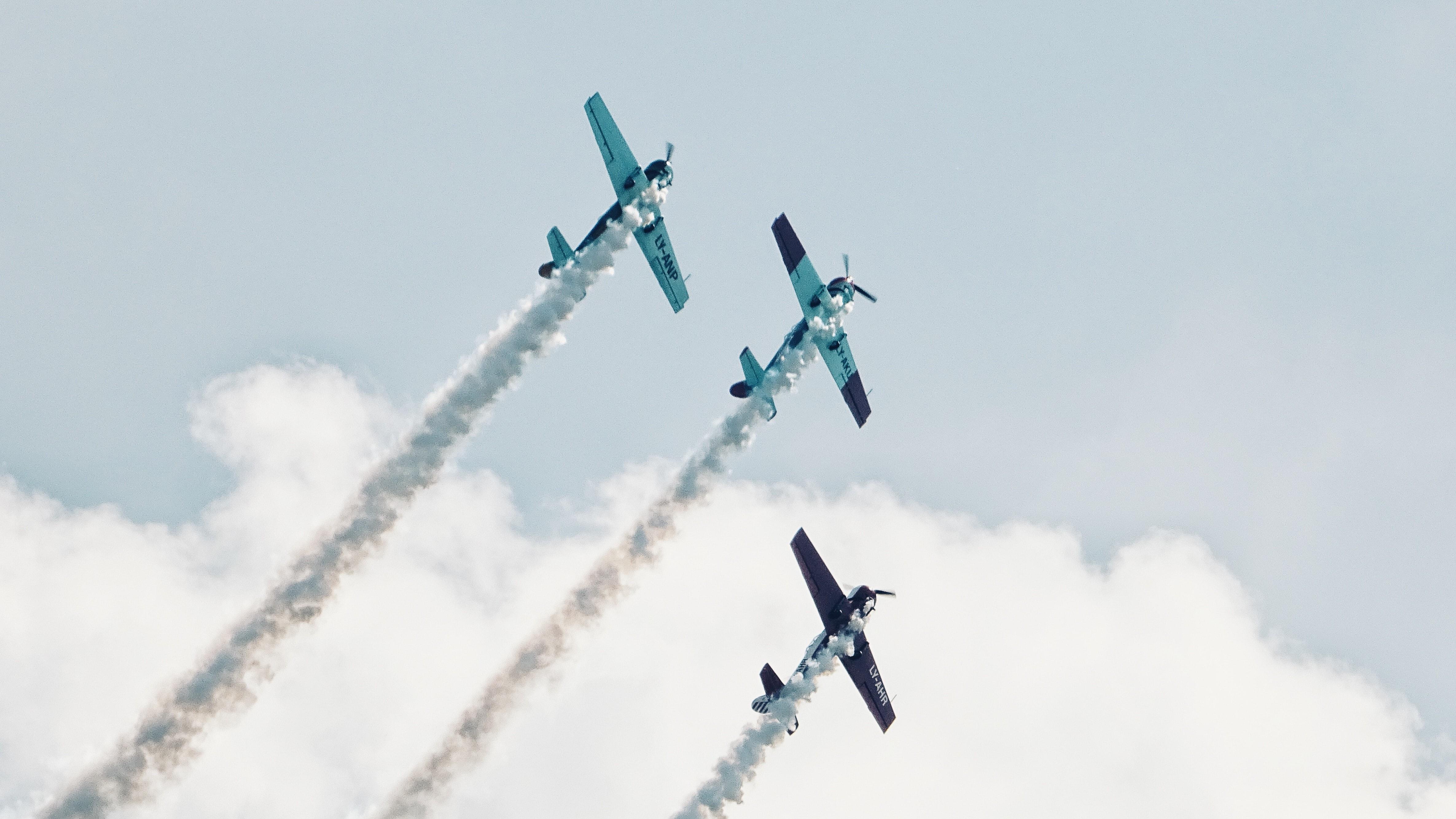 Three small planes leaving white smoke trails behind at an air show