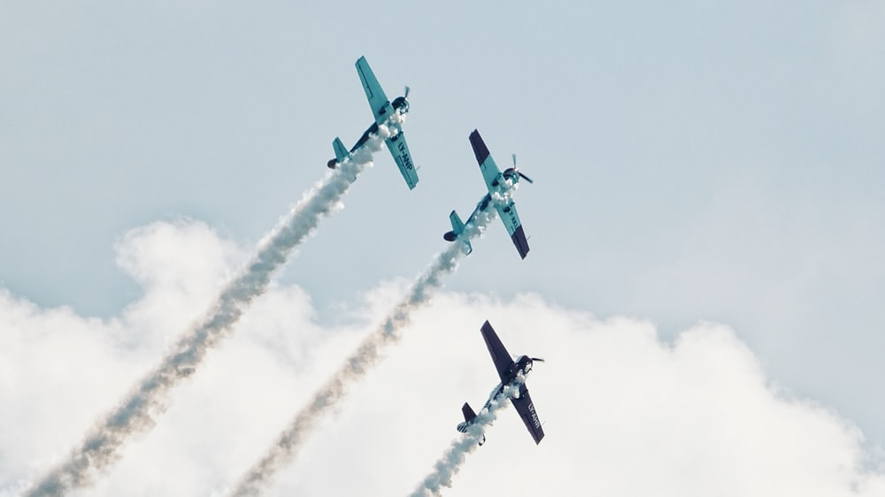 three gray plane showing smoke