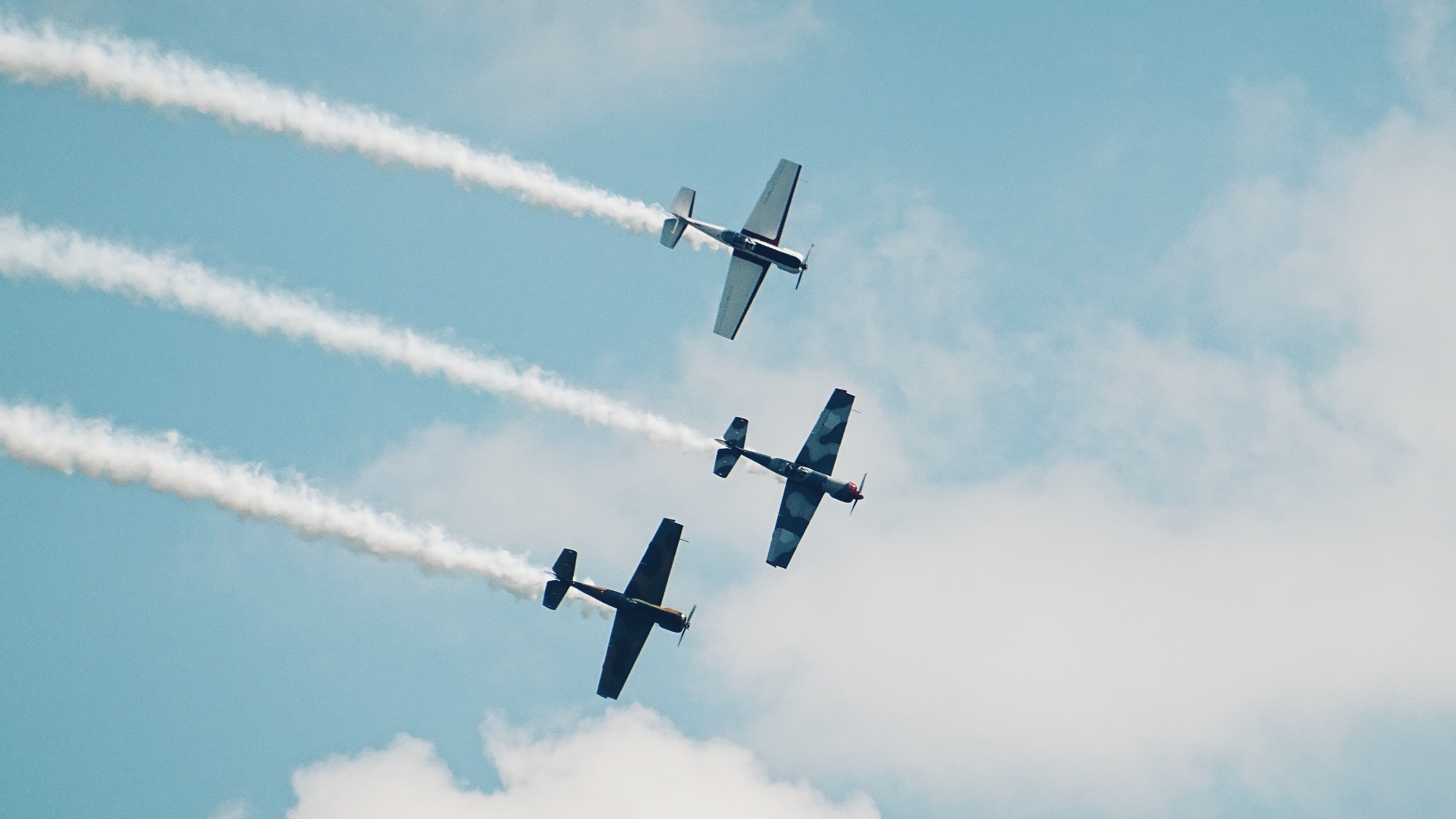 Ground perspective of three vintage planes flying in formation, with smoke trails emitting from the rear.