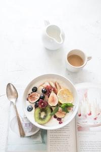 white ceramic plate beside gray steel spoon
