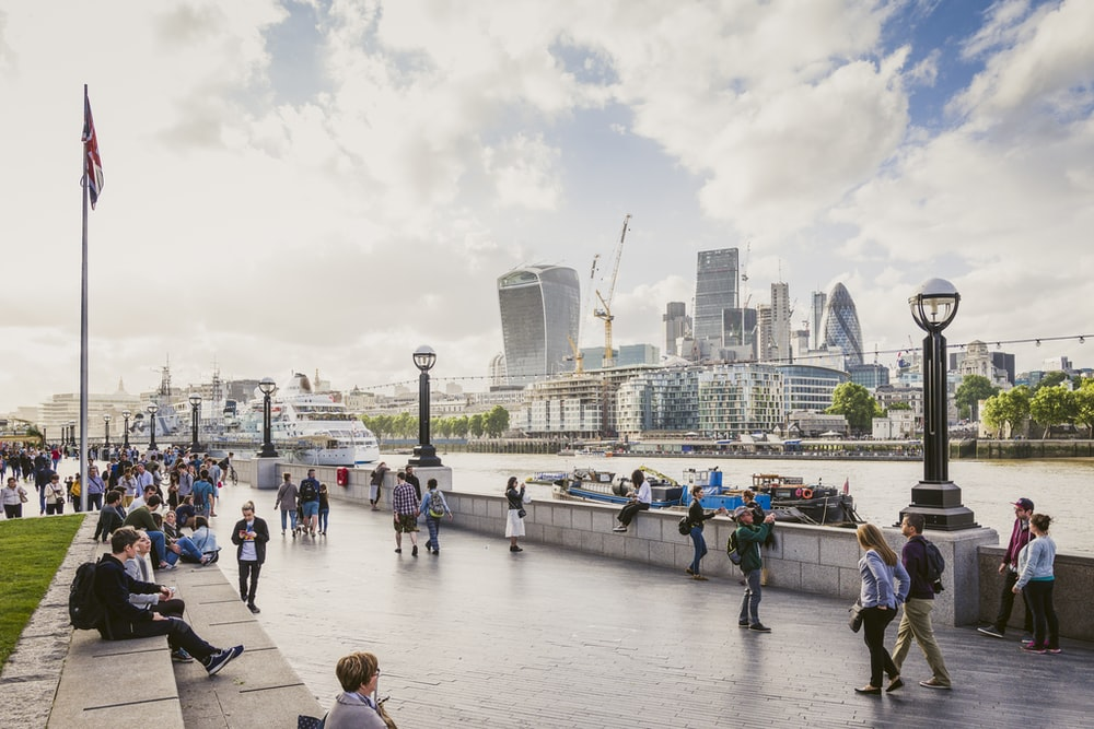 Tourists strolling on the bank of Thames with the City of London visible on the other shore