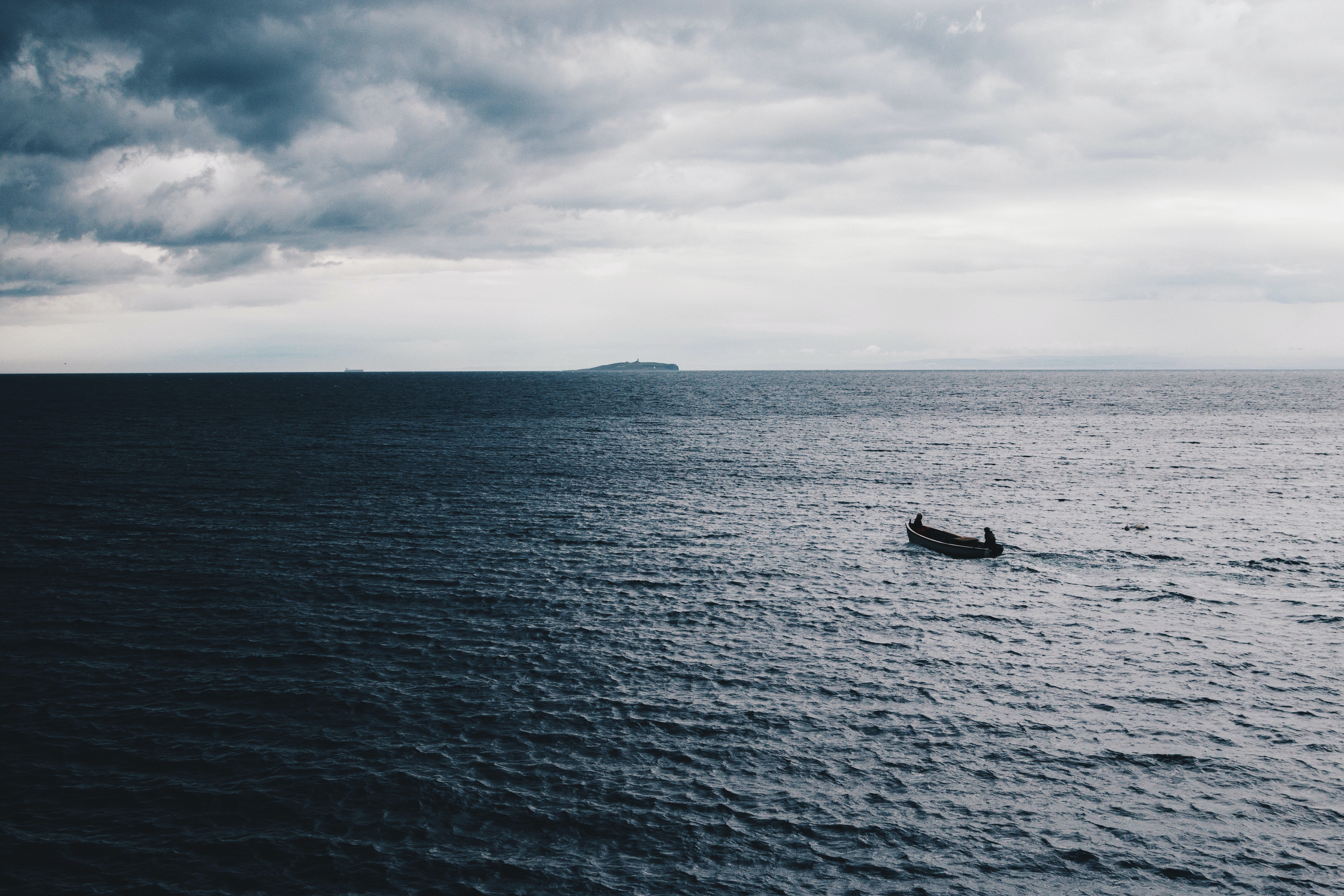 low-light photography of boat on ocean water under cloudy sky