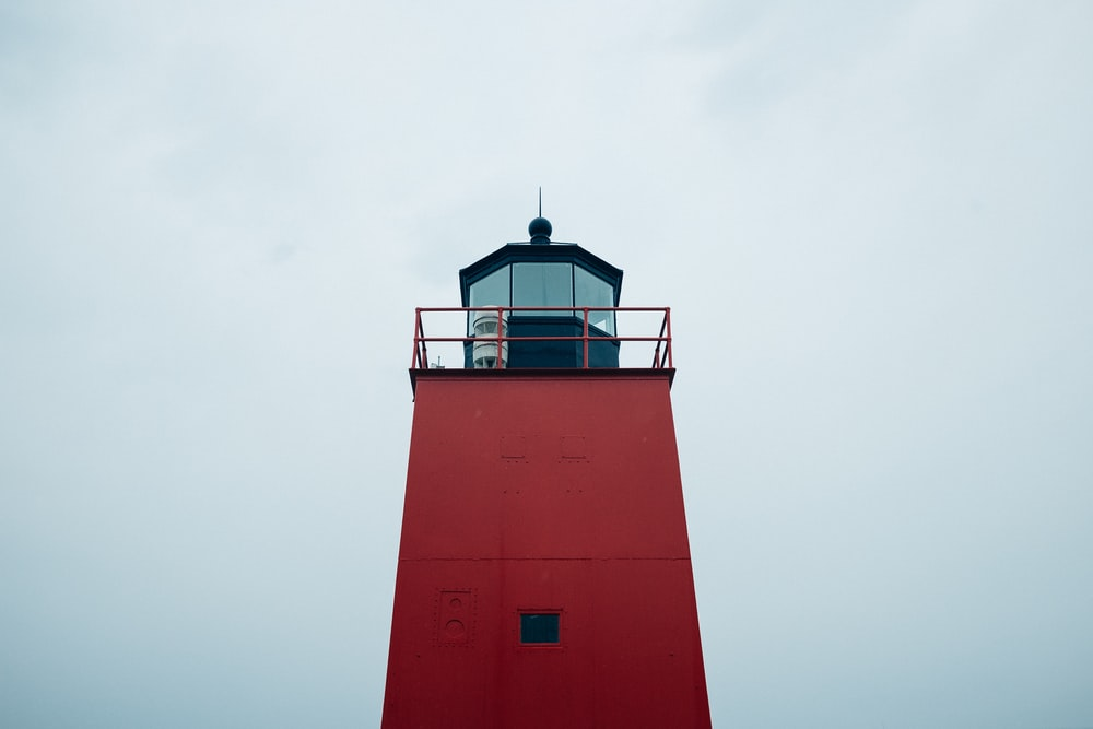 low-angle photograph of red lighthouse