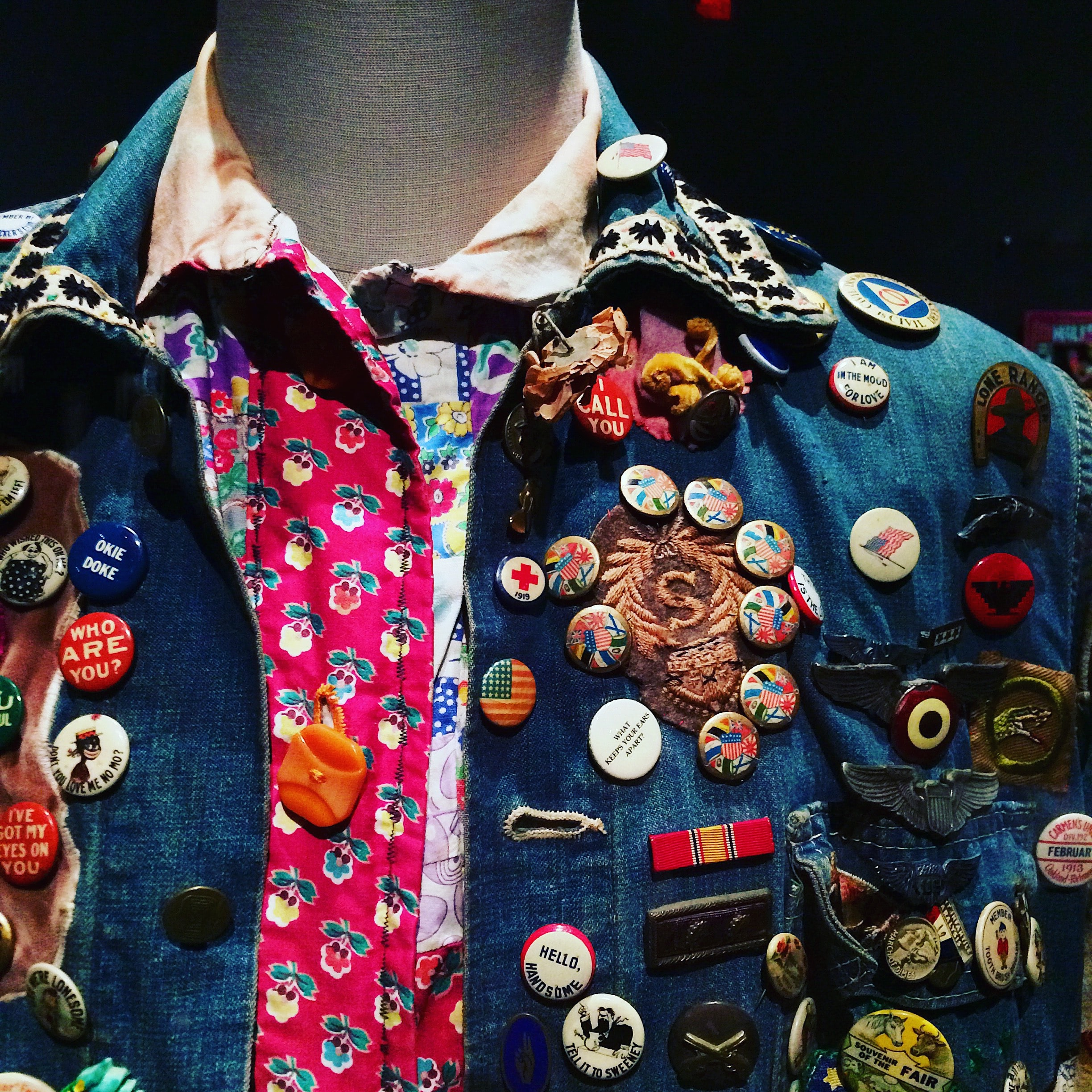 A dummy with a colorful button-up shirt and jean jacket covered in pins at a museum