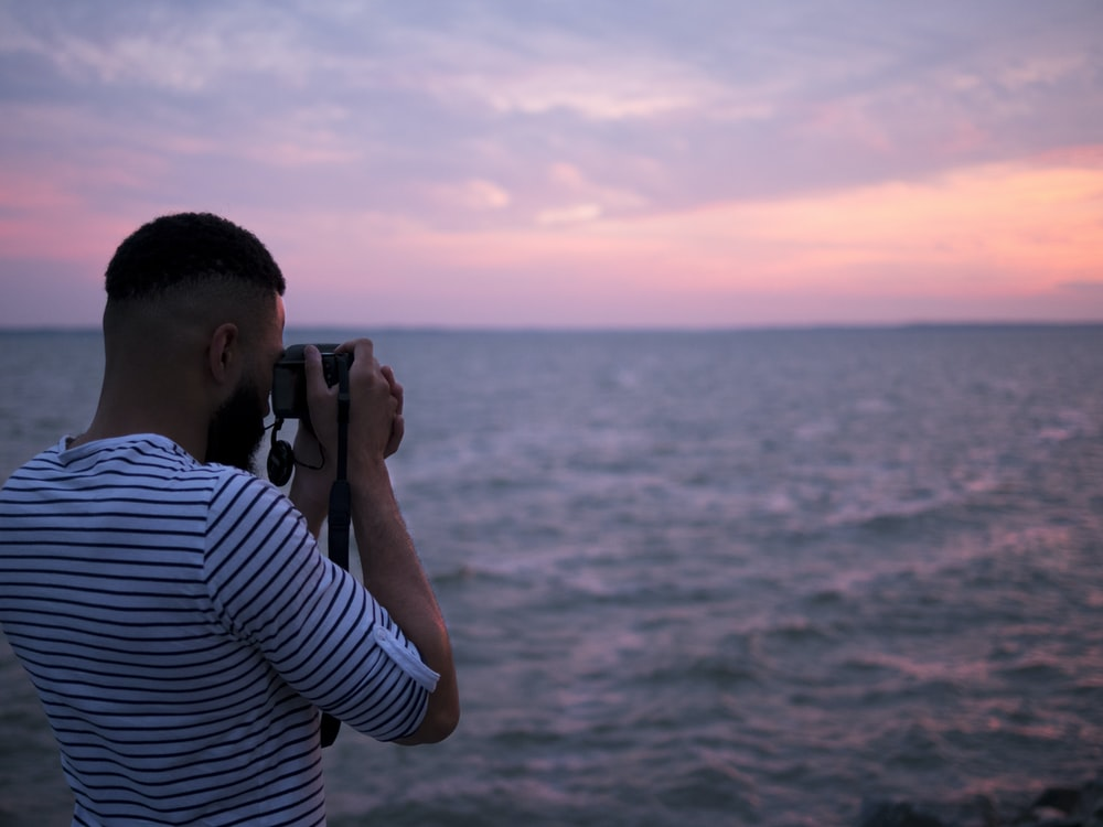 A man in a striped shirt taking a picture of the ocean.