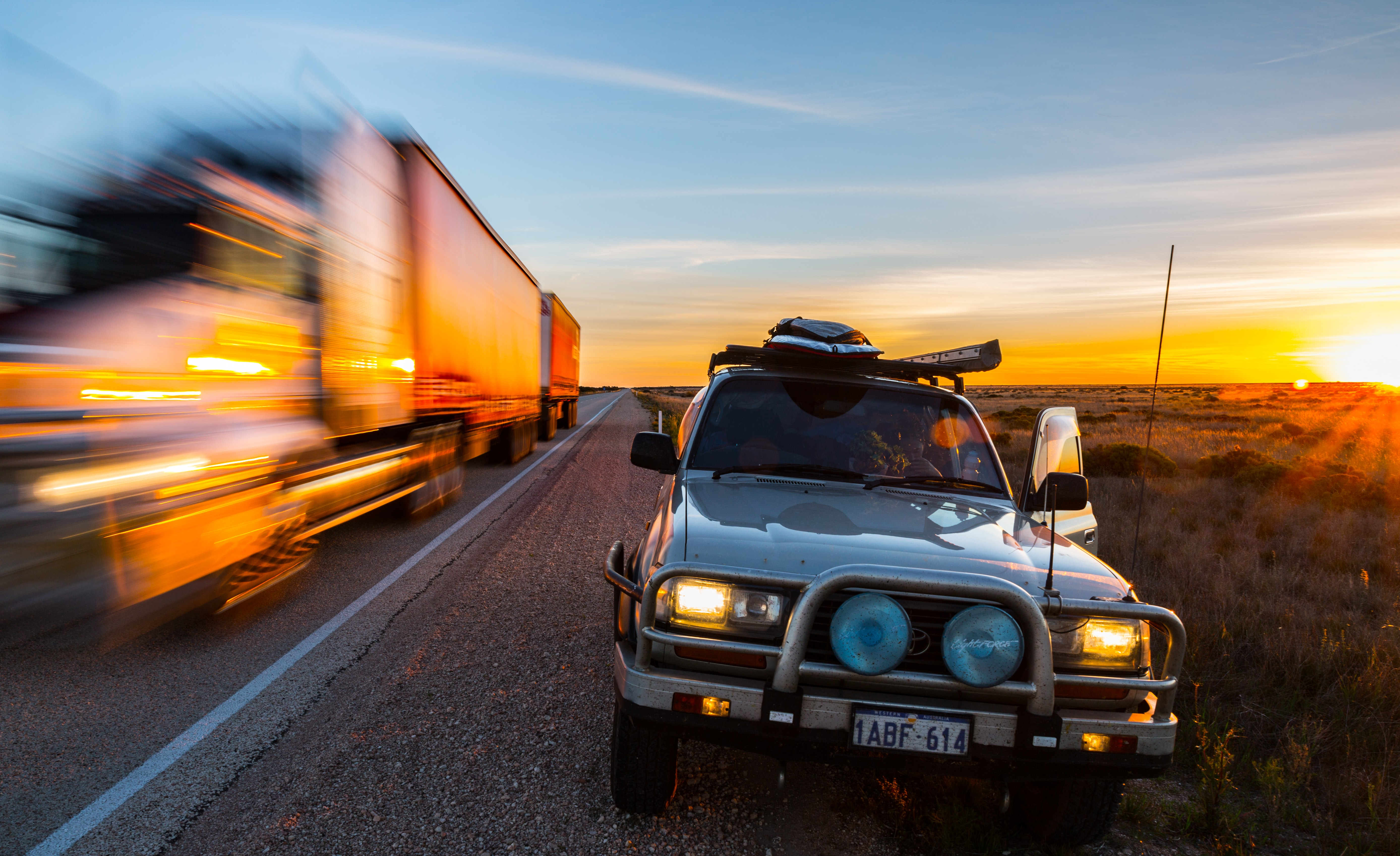 A view of a car parked on a roadside while a truck is moving next to it in Nullarbor