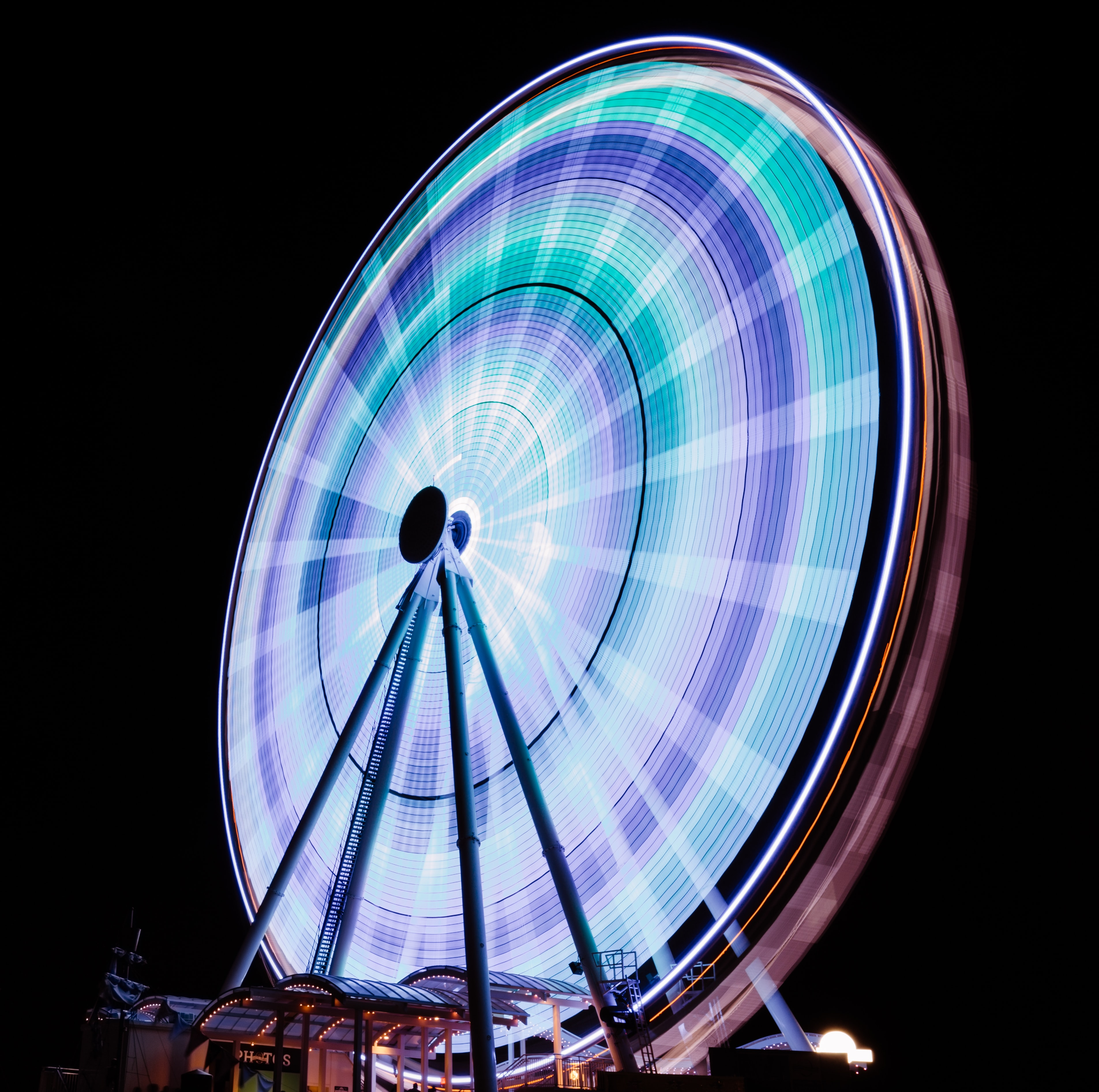Long exposure photography of the Ferris wheel at National Harbor at night.