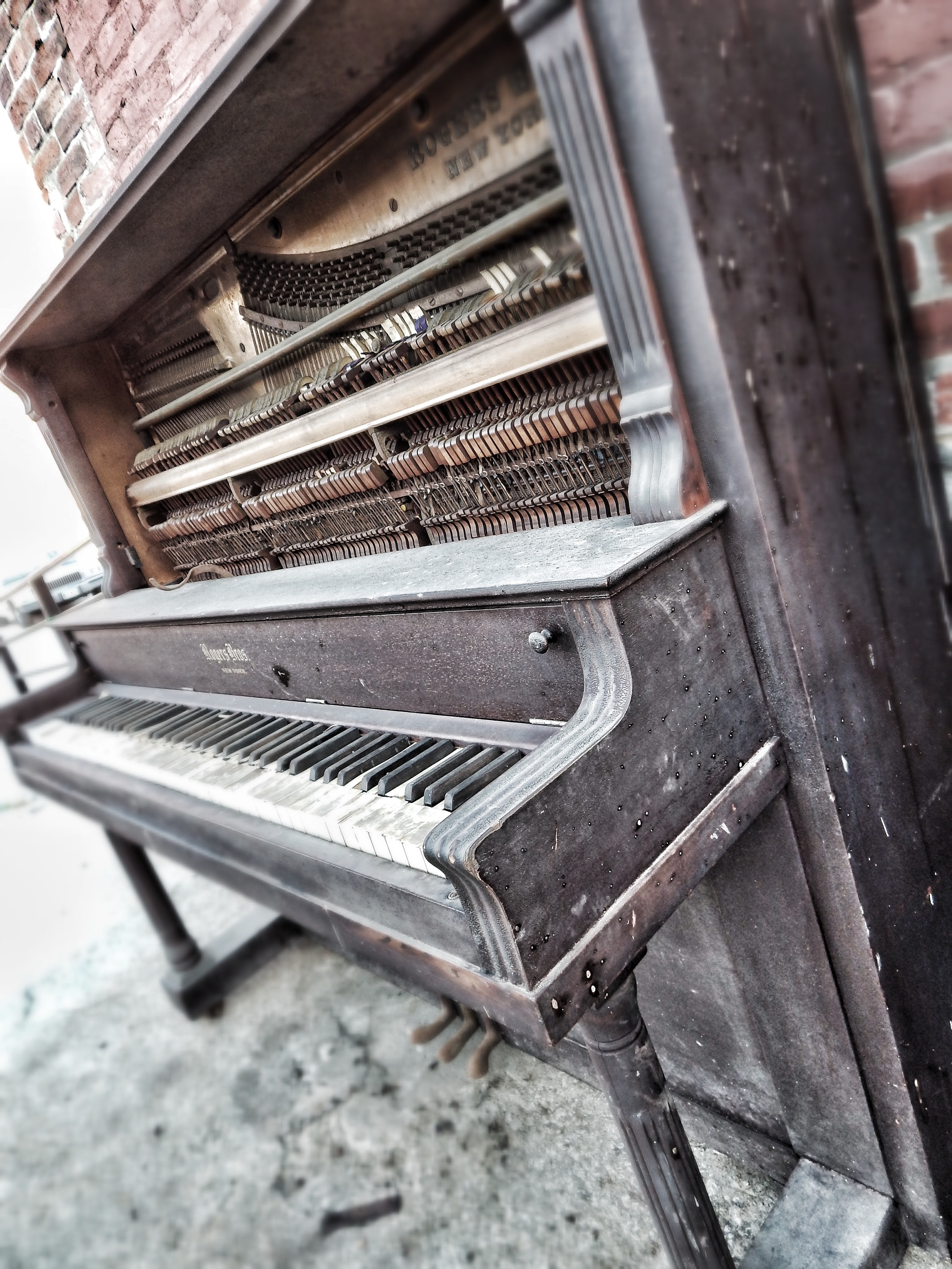 An antique wooden piano by a brick wall in West Bottoms.