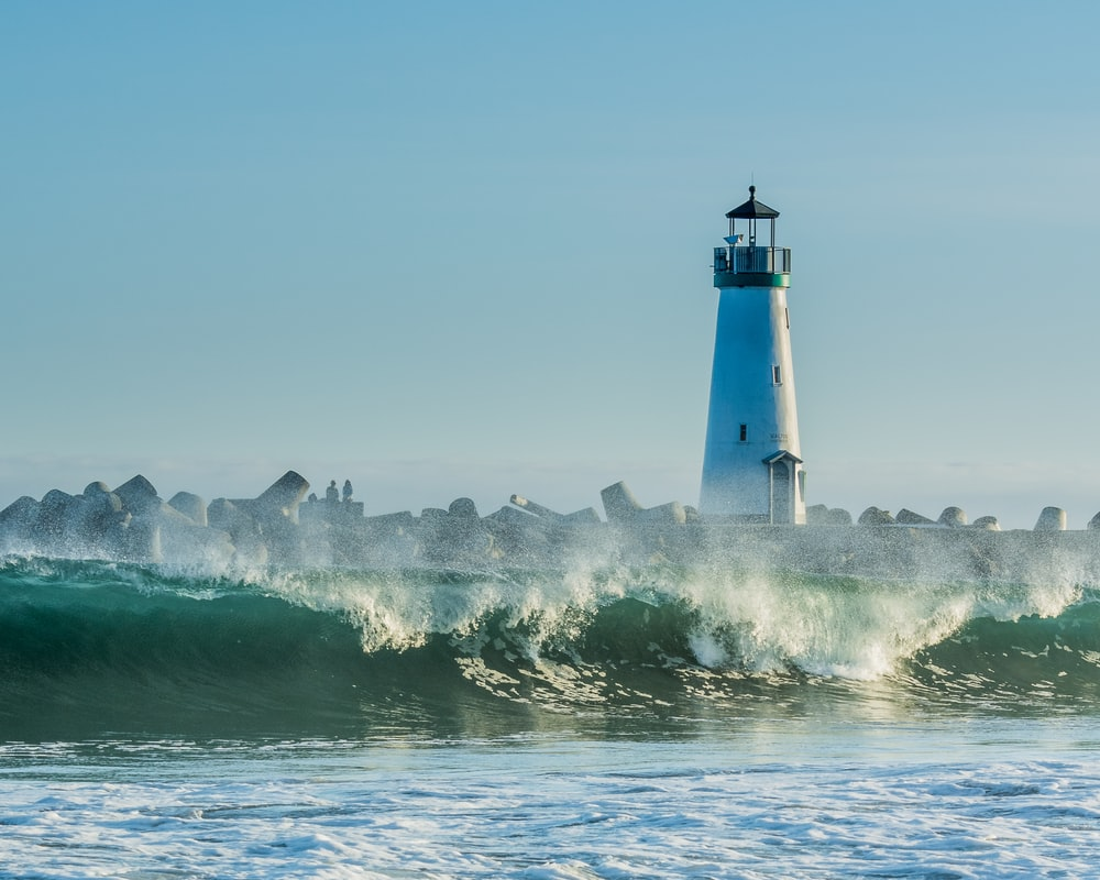 concrete lighthouse near rocks and ocean wave at daytime