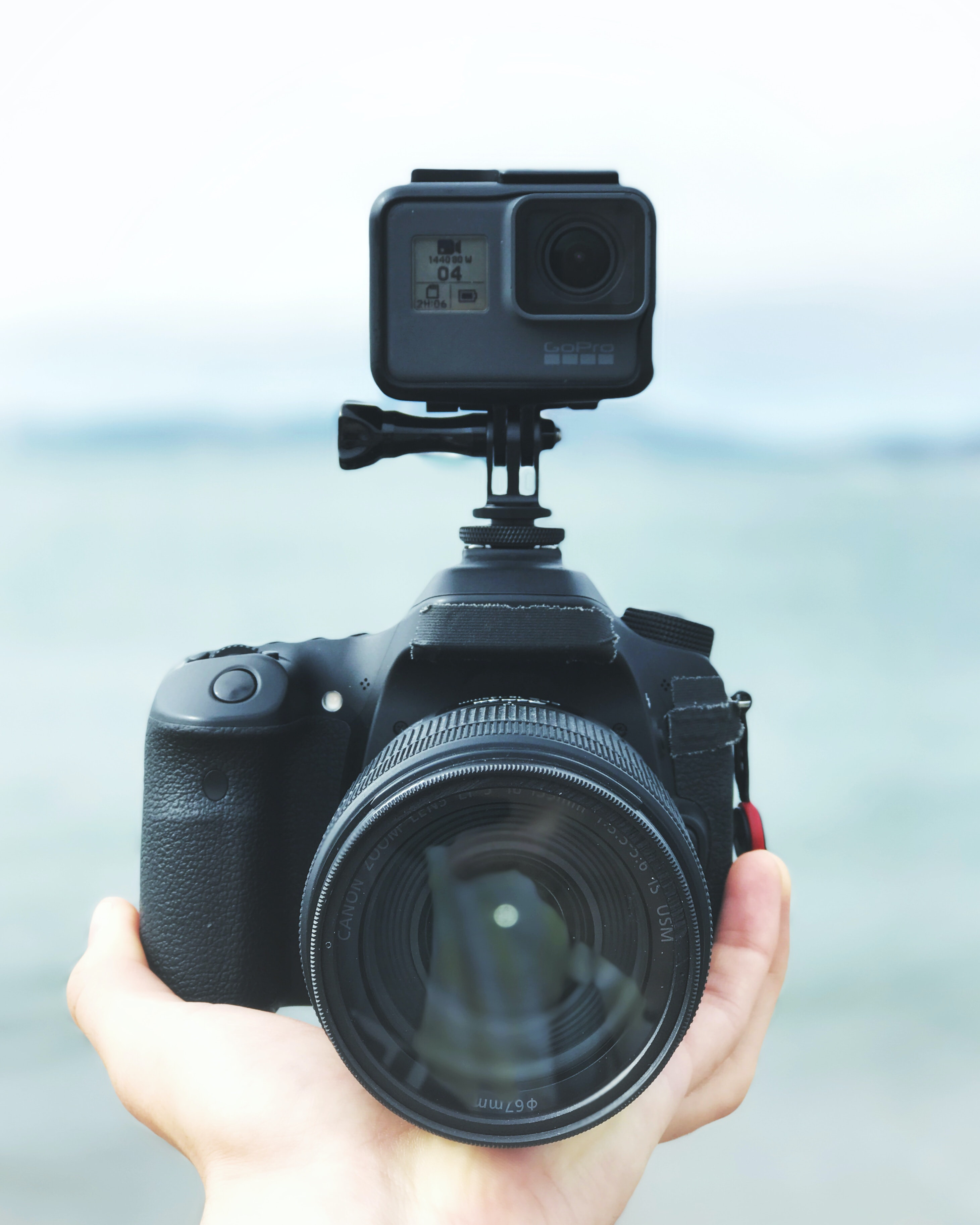Macro of a person holding a black DSLR camera with a GoPro mounted on beside a lake or sea setting