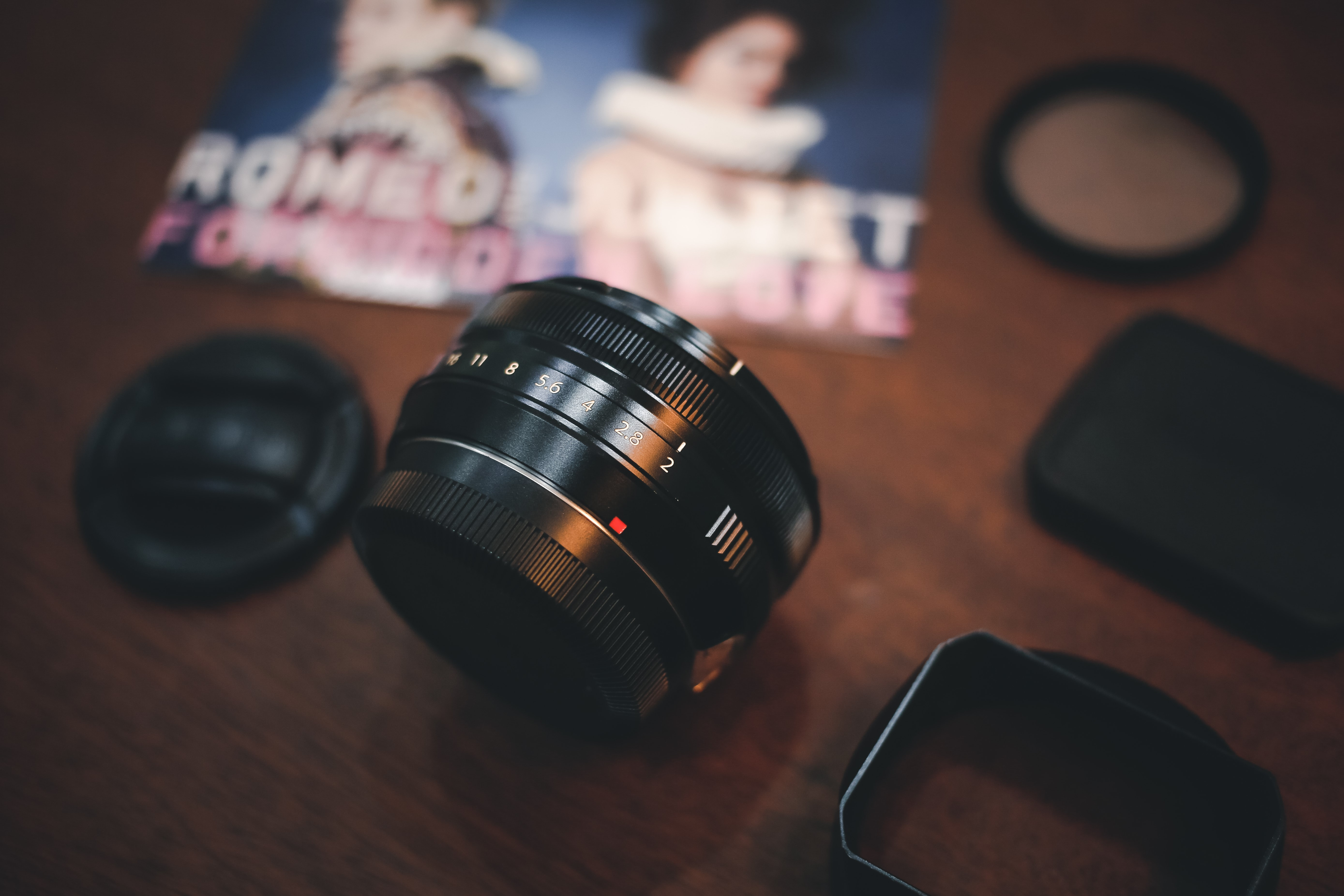 A macro of a DSLR camera lens beside a romeo and juliet print and various covers.