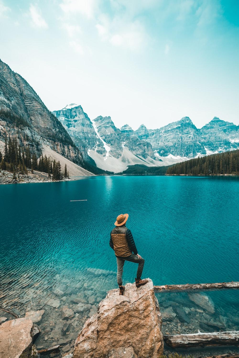 man standing on rock near lake