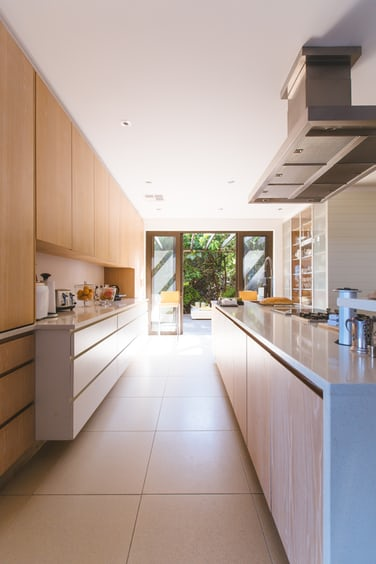 Clean, modern kitchen with window looking out on trees and sunlight