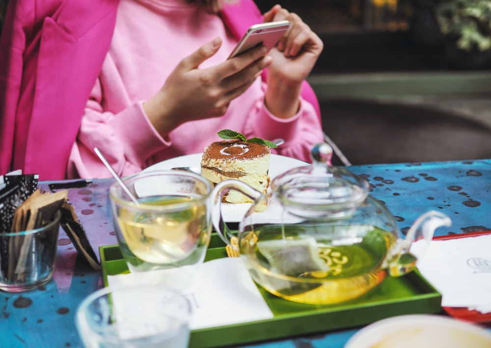 woman sitting beside table holding gold iPhone 6 while having tea
