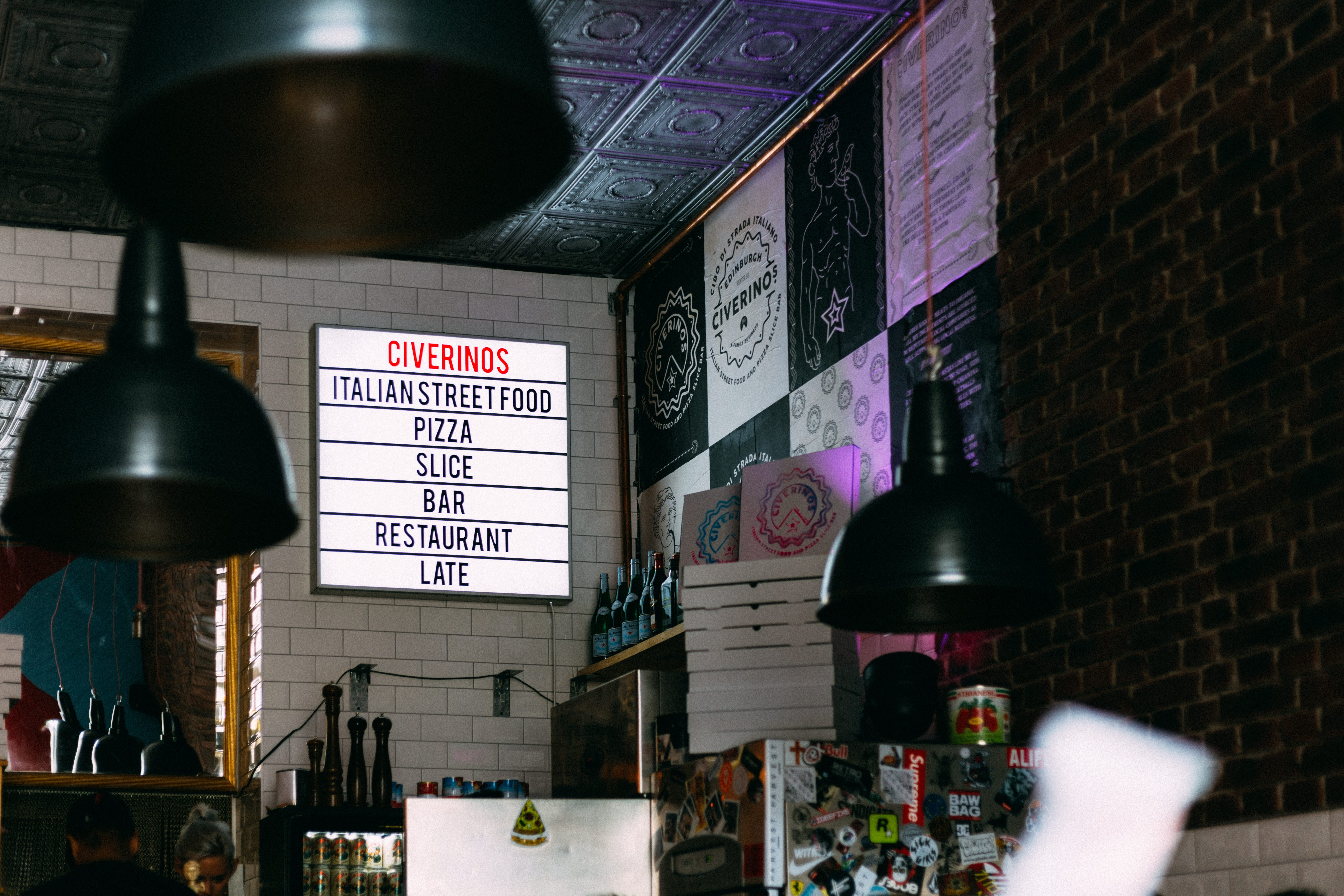 The walls of a bistro with signs, posters, and refrigerators