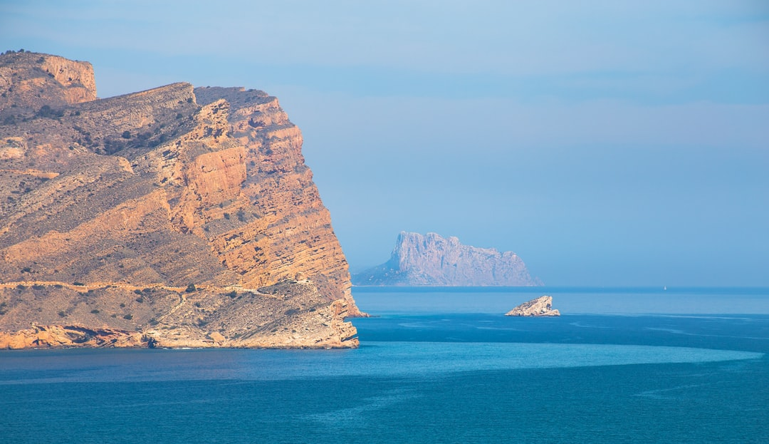 I shot this whilst on holiday in the south of Spain last year. The mainland is El Morret Negret, the little island is Illeta Penyes d'Arabí and the mainland in the distance is Ifach National Park. Looks prehistoric!
