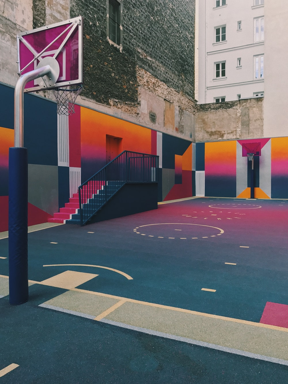 black, purple, and orange basketball court beside concrete buildings at daytime