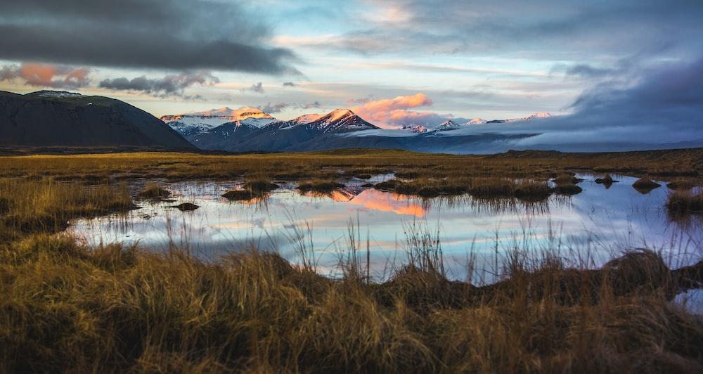 body of water between grass field far from mountain