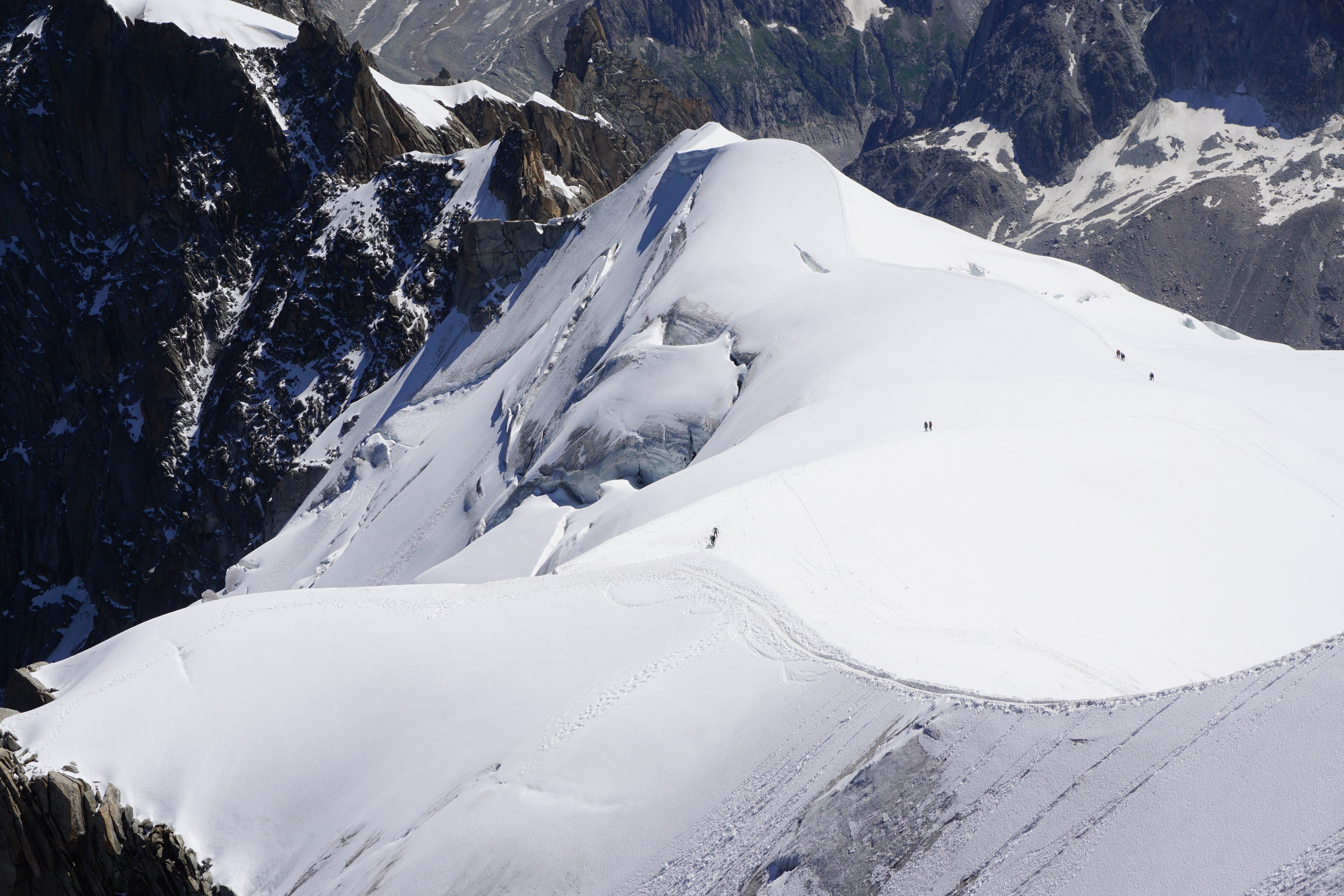 Deep snow covers slopes and cliffs of mountains