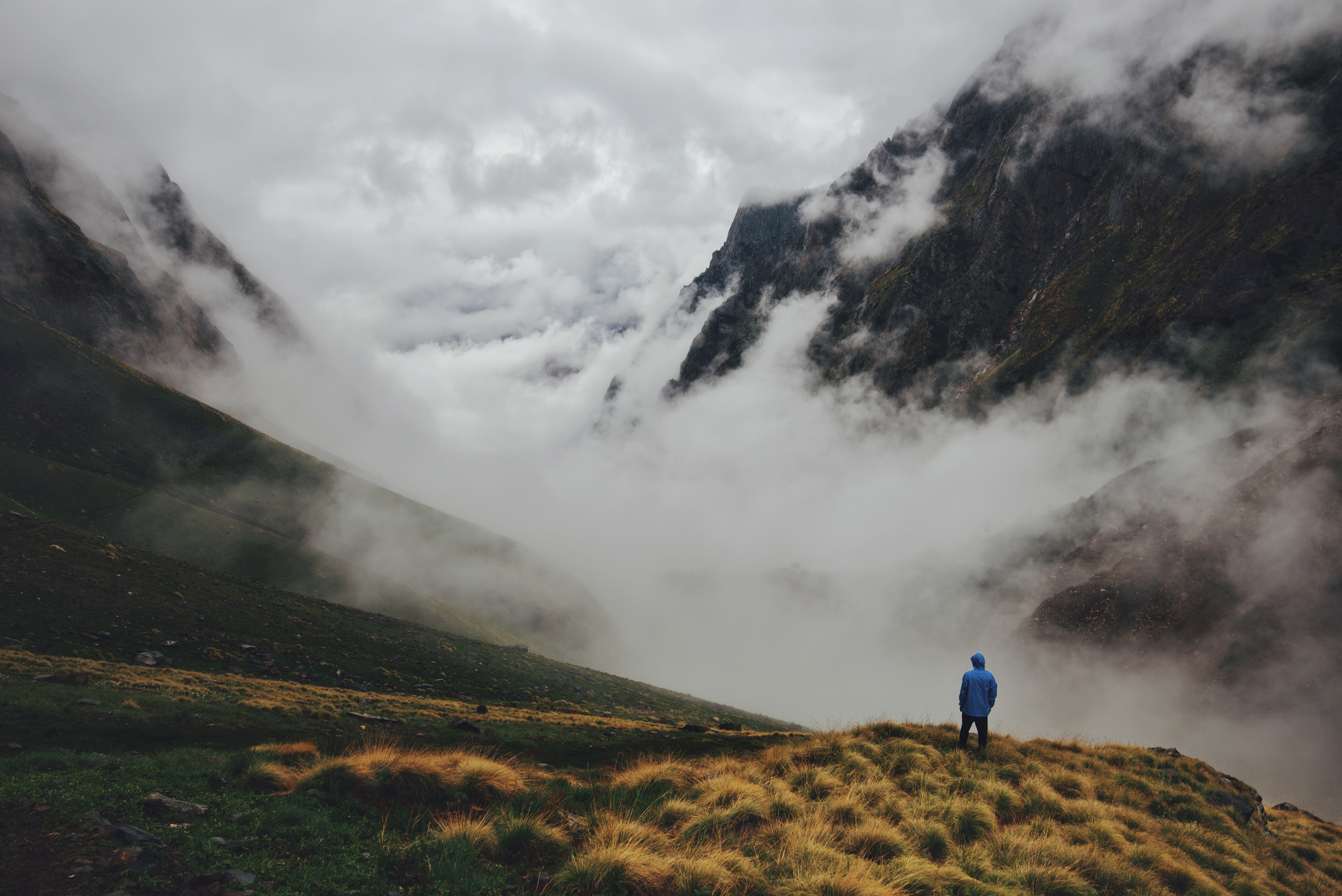 aerial photography of hooded man standing at mountain cliff facing cloudy mountains