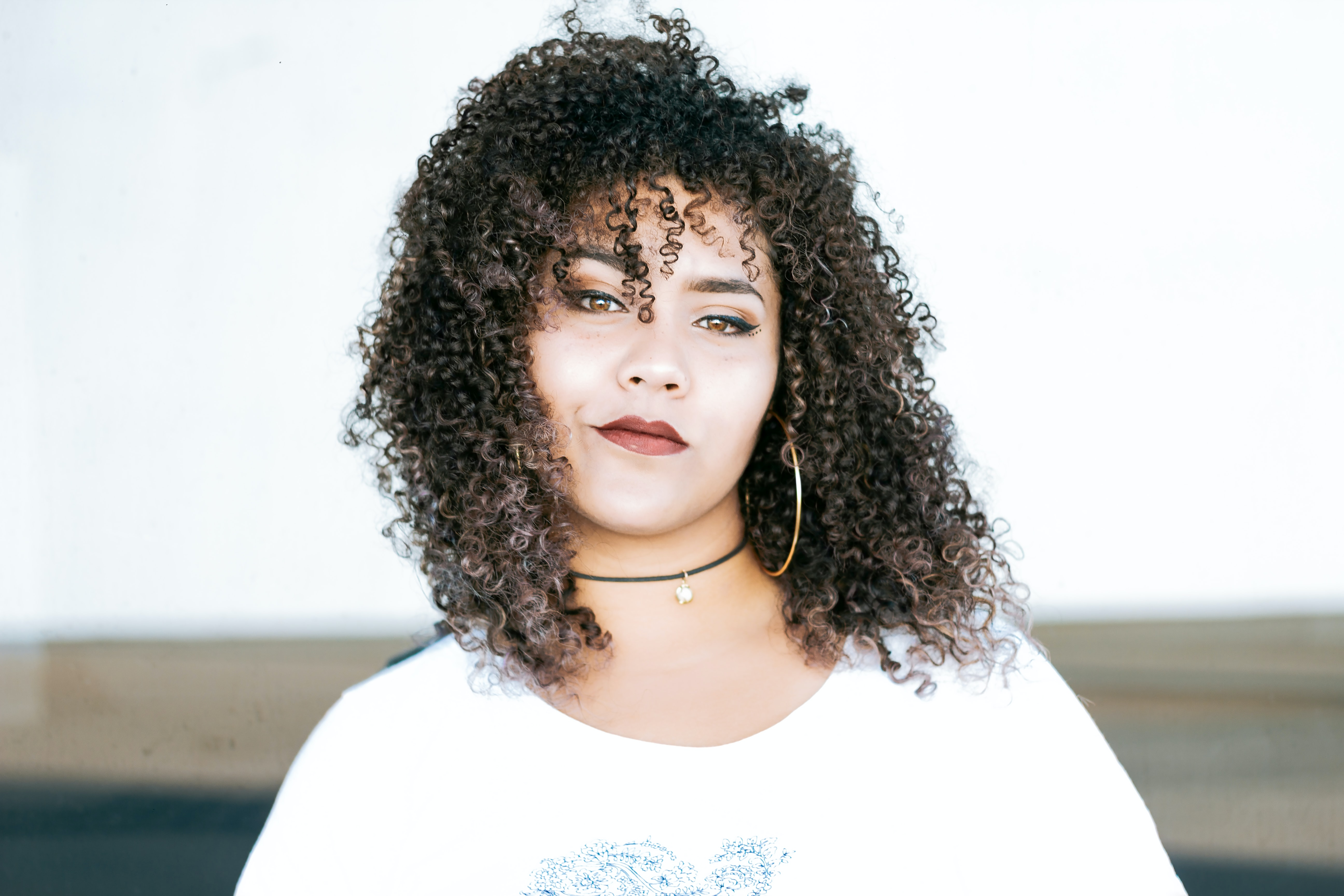 Woman with curly hair smiles confidently