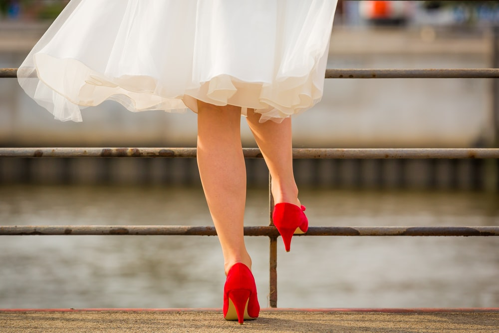 woman wearing white mini dress and red platform pumps standing on gray concrete pavement beside body of water during daytime