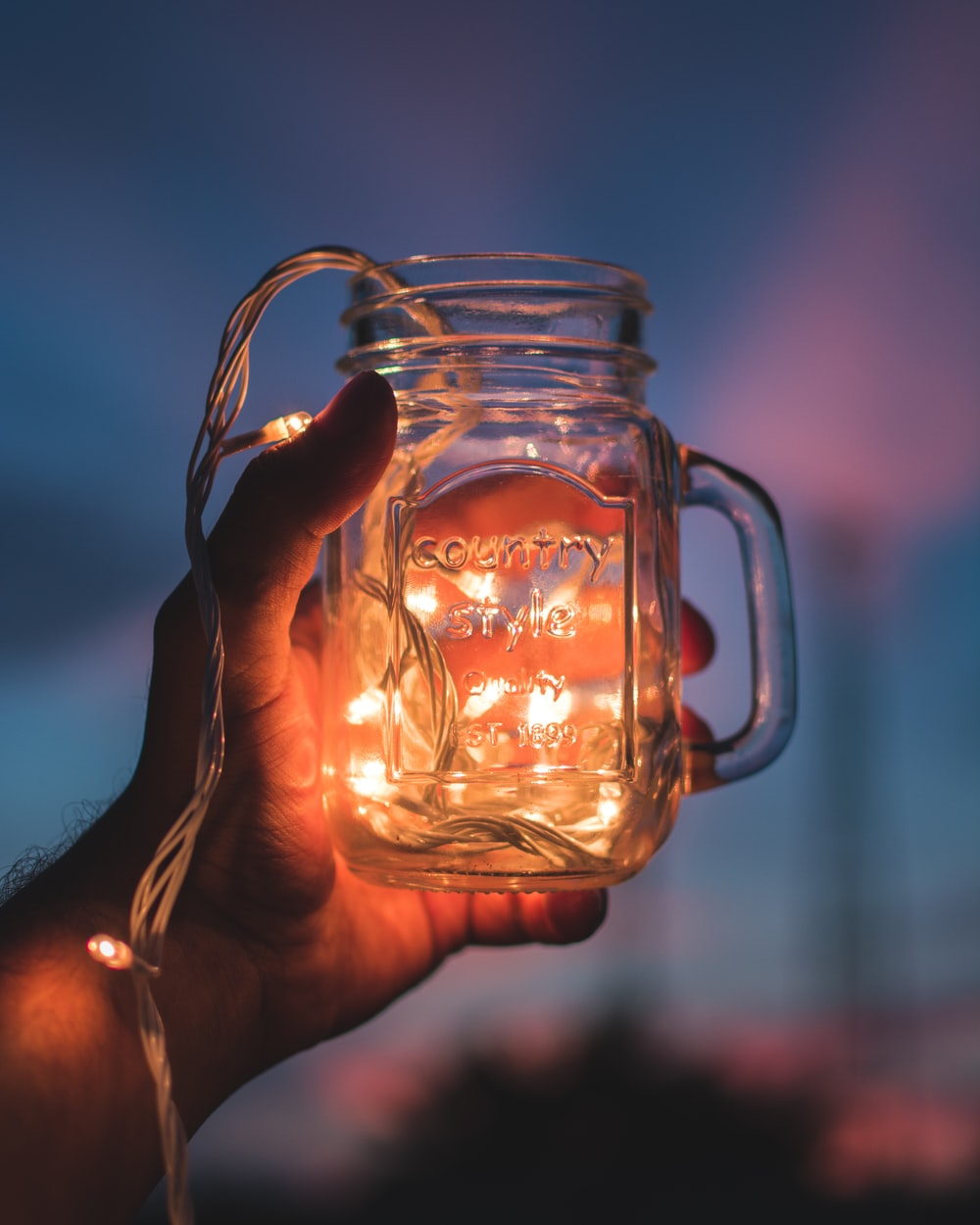person holding jar with lighted string lights