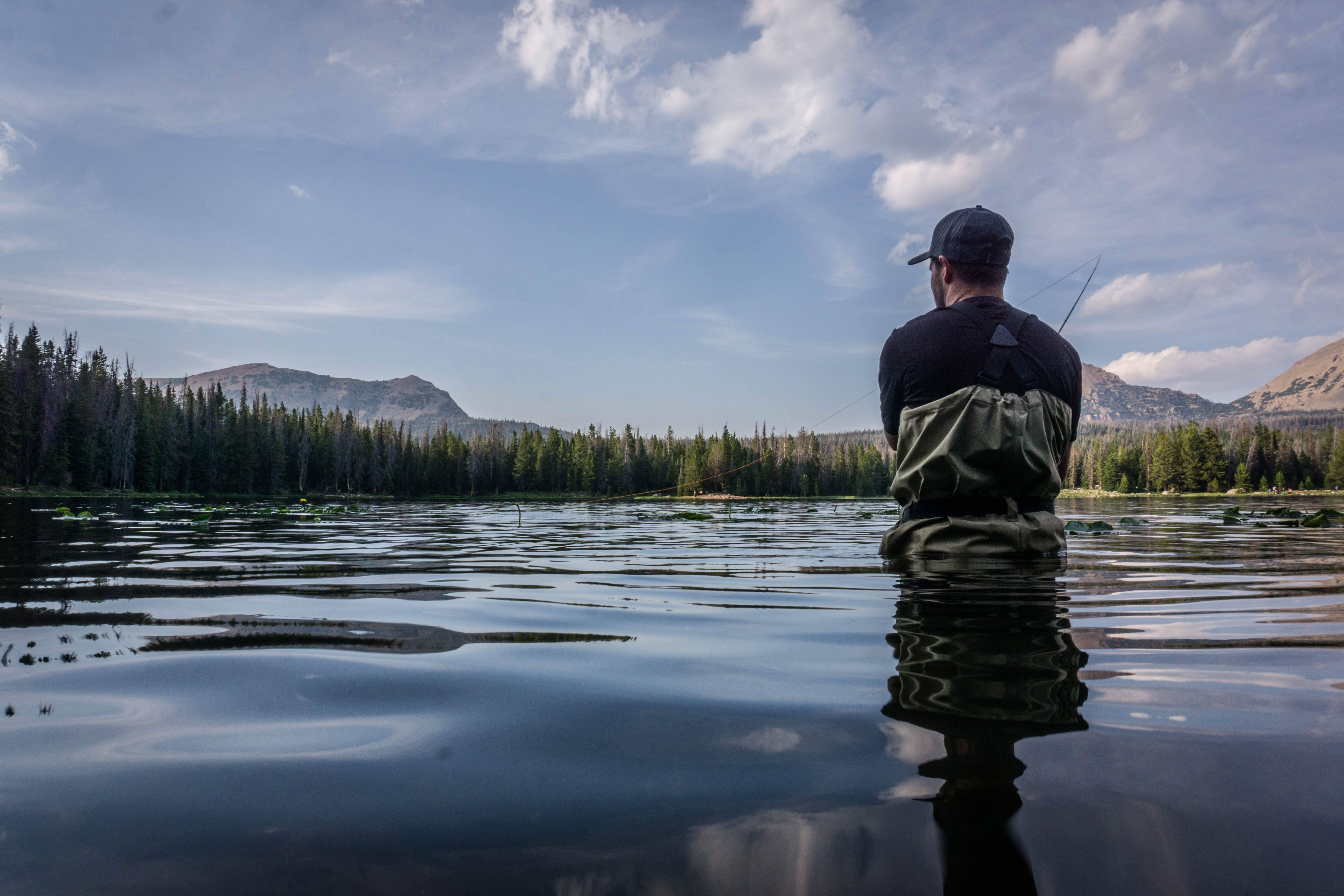 man in black and gray shirt wearing cap on body of water during daytime