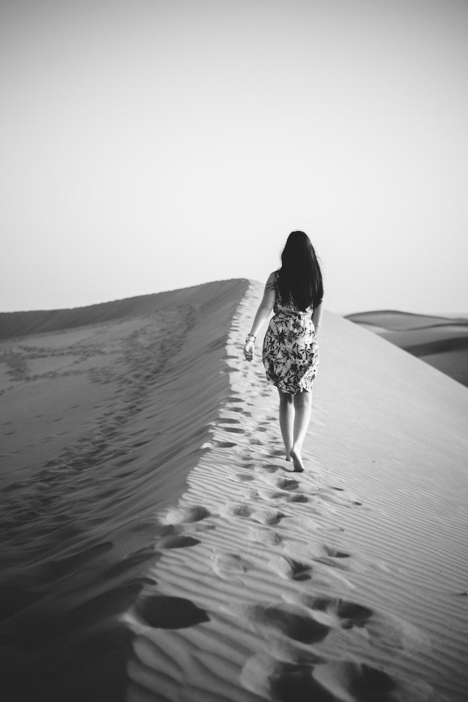 昼間に砂漠を歩く女性のグレースケール写真