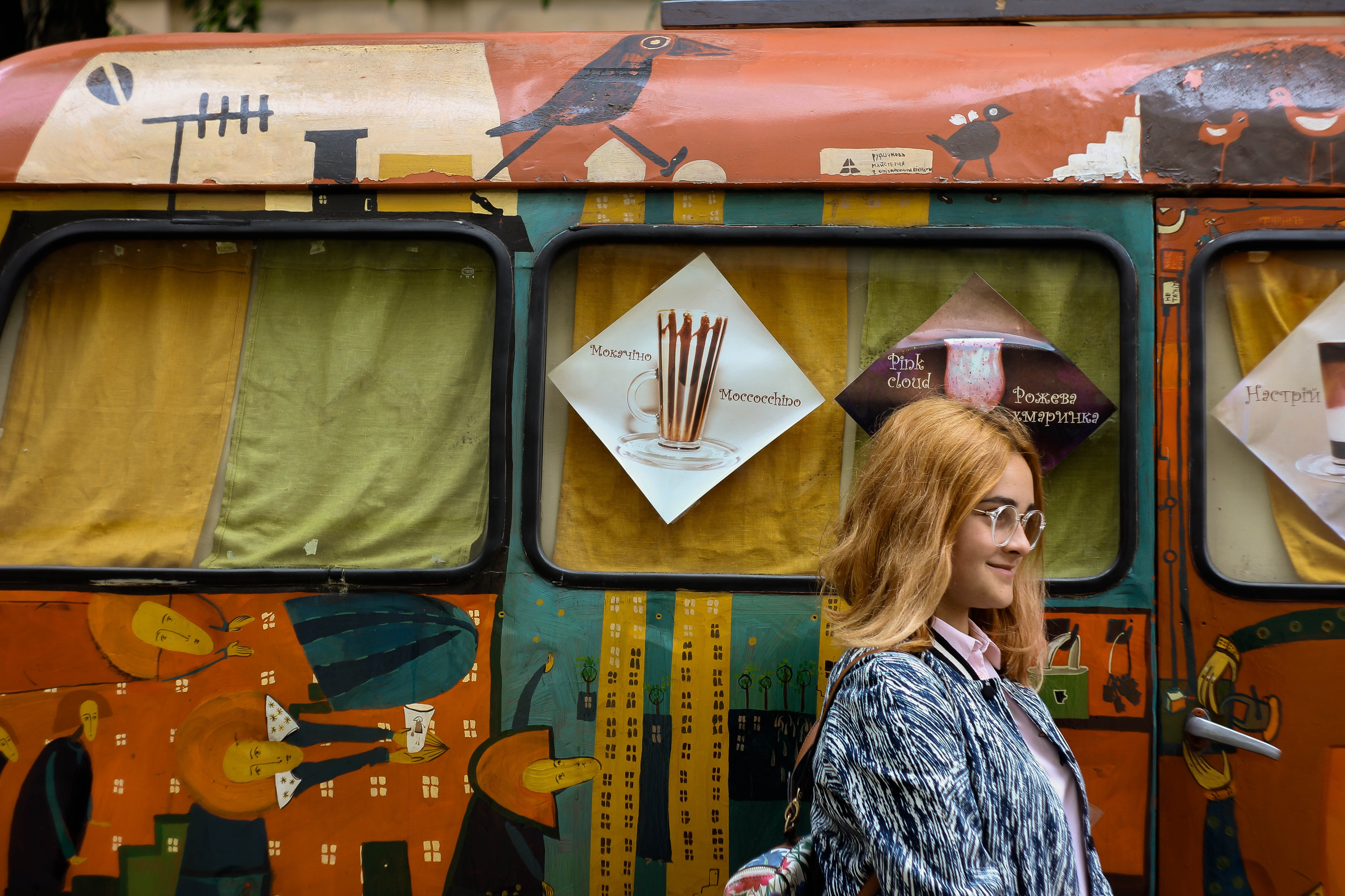 A stylish smiling woman in glasses walks by a bright, intricately decorated bus