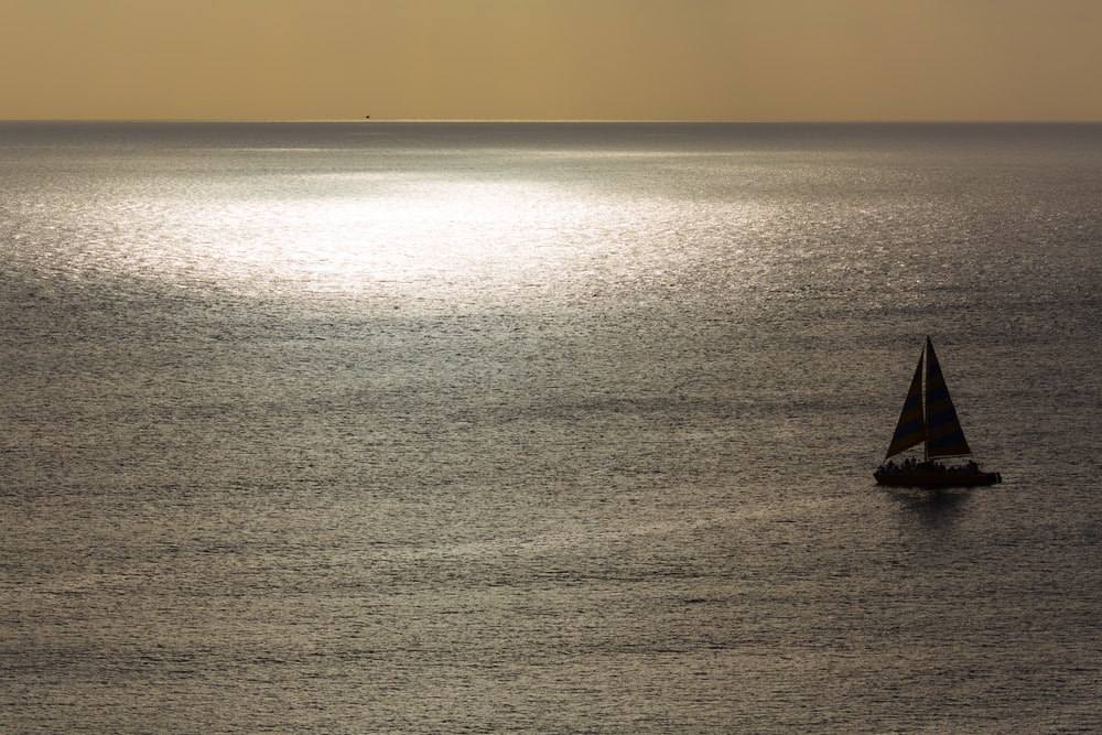 silhouette photo of sailboat on calm body of water