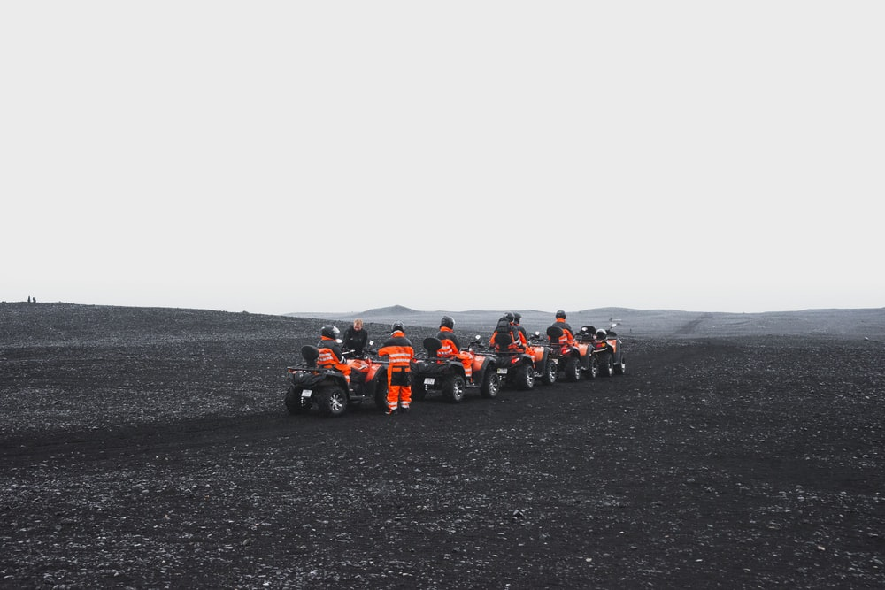 group of people in orange suit riding a ATV