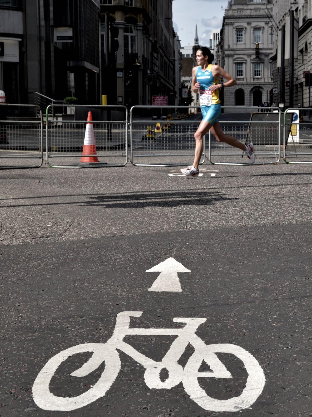 woman running on gray concrete pavement taken at daytime