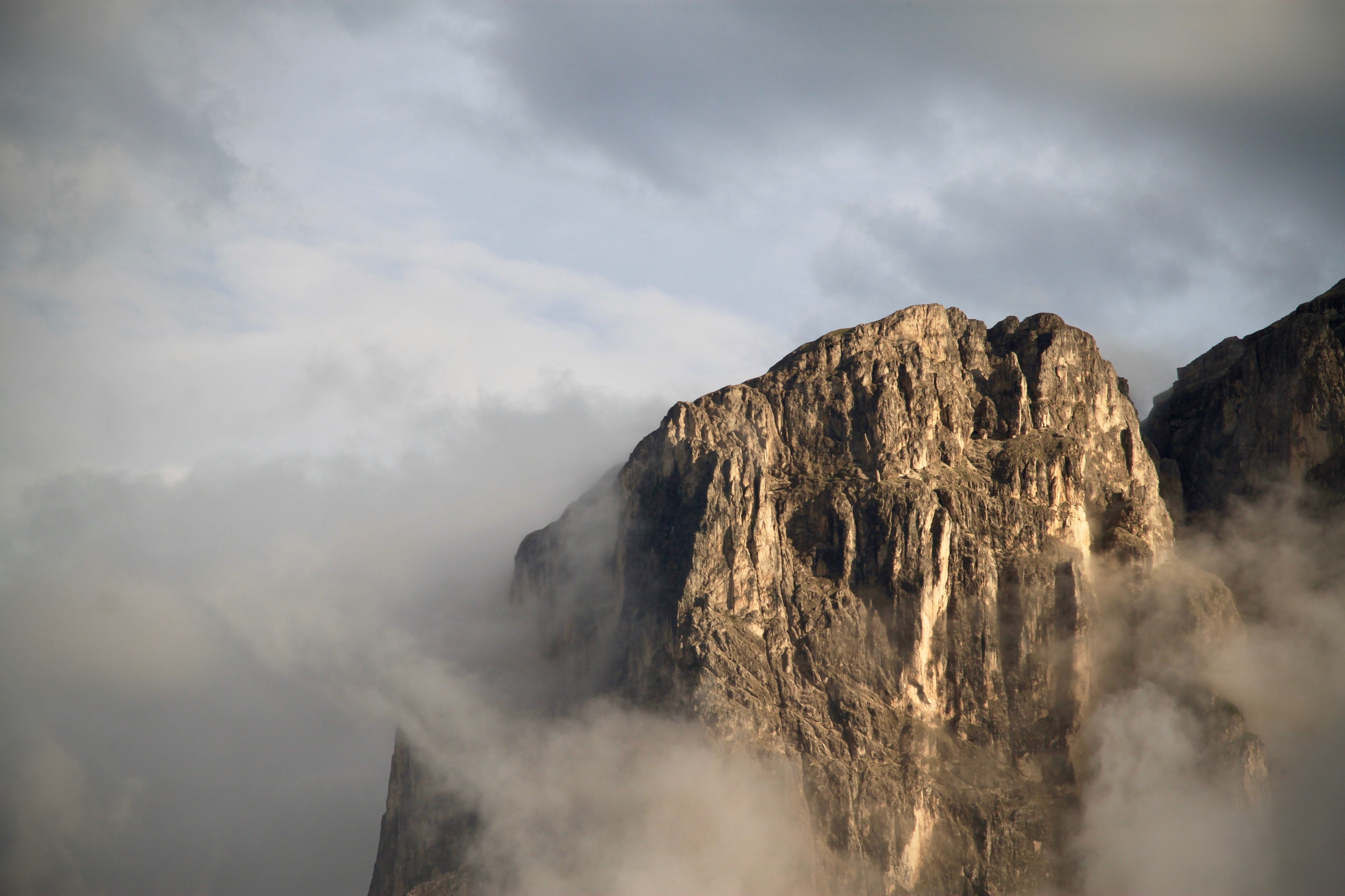 photo of gray rock formation covered in cloud