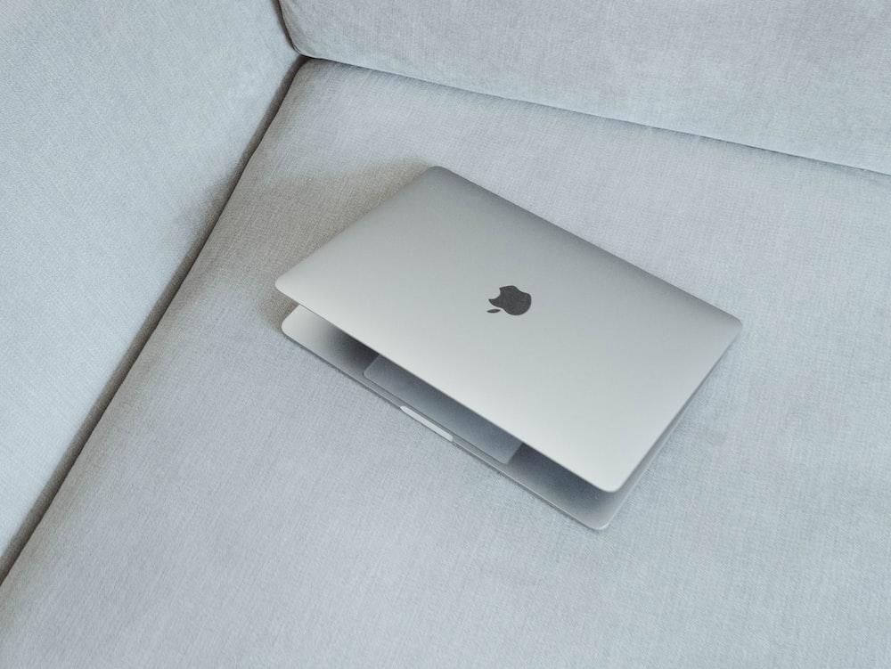 silver MacBook on white fabric sofa