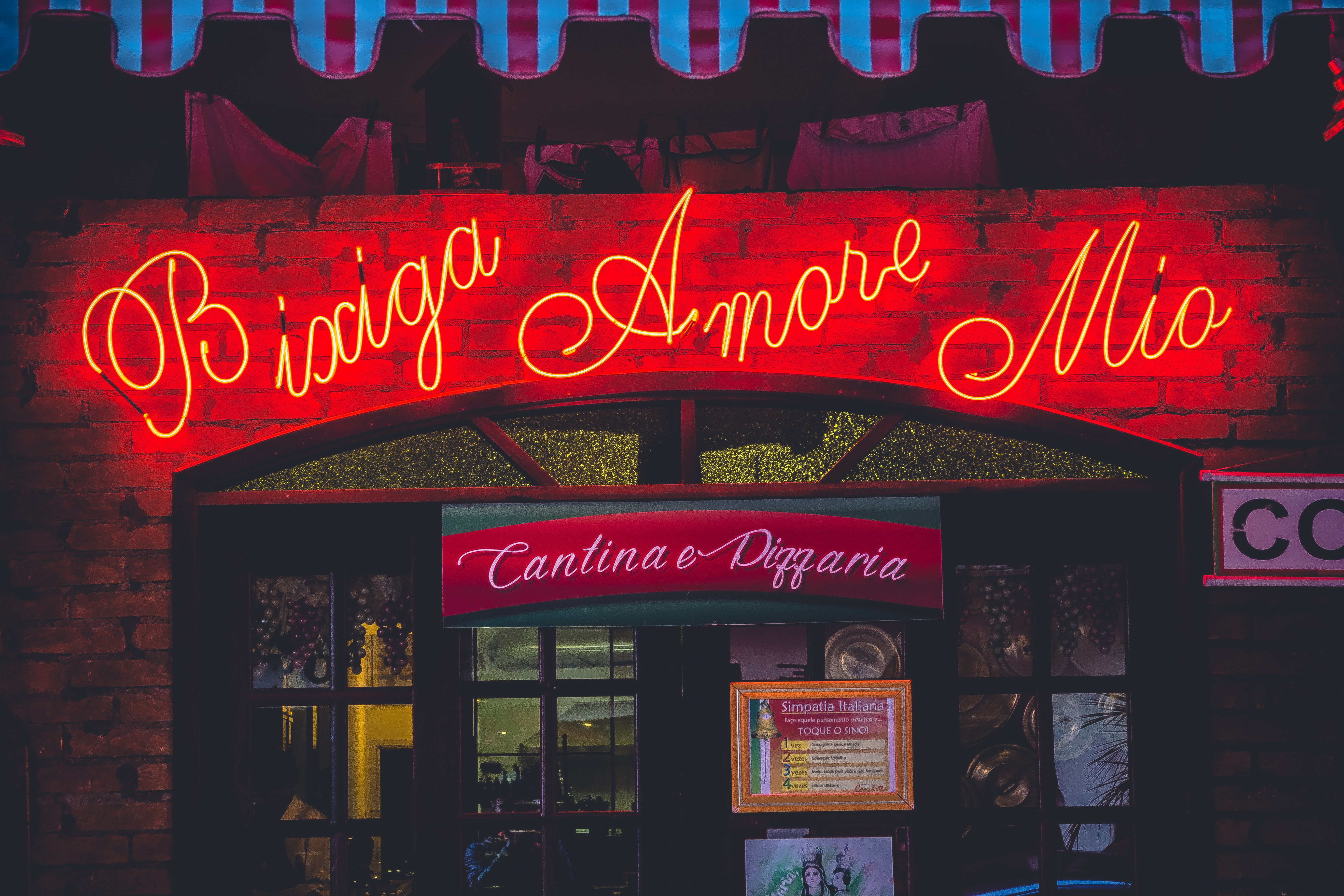 An Italian restaurant storefront with a red neon