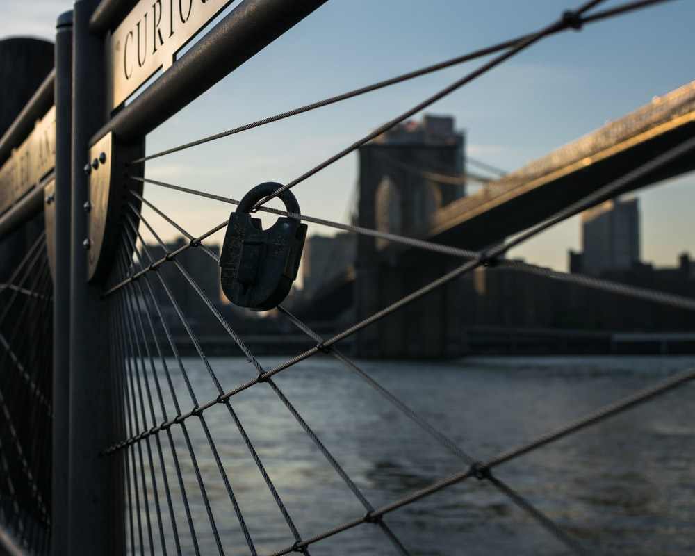 gray padlock on fence