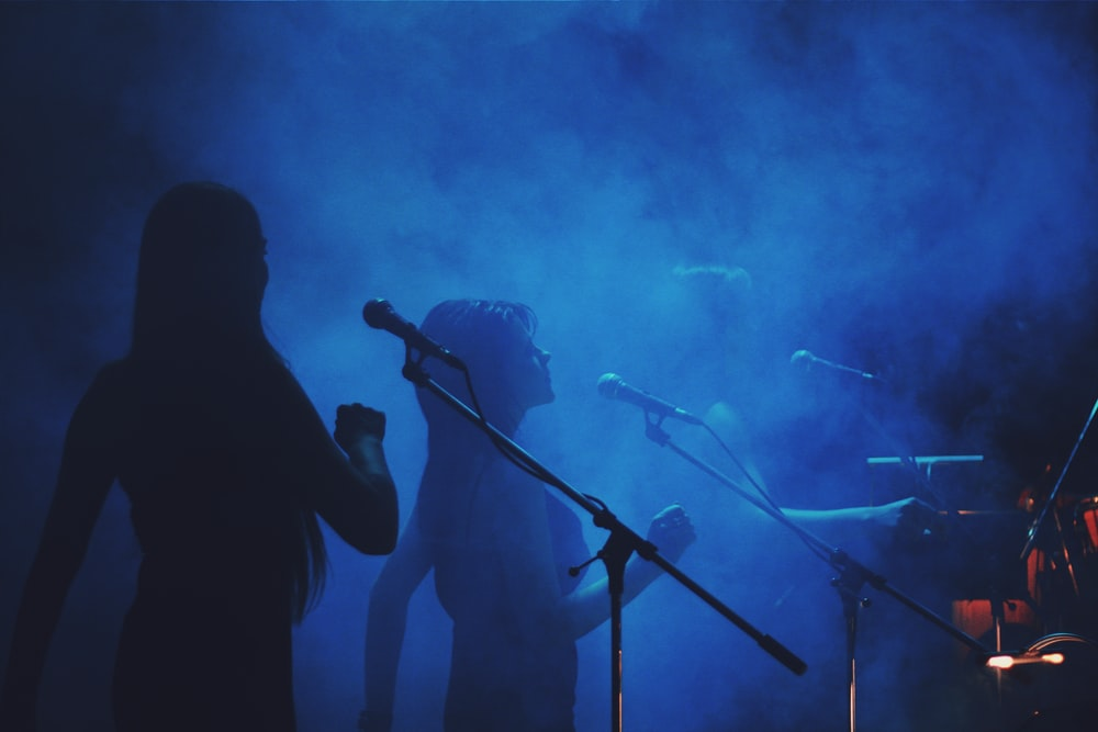 silhouette photography of three women standing in front of microphone stands