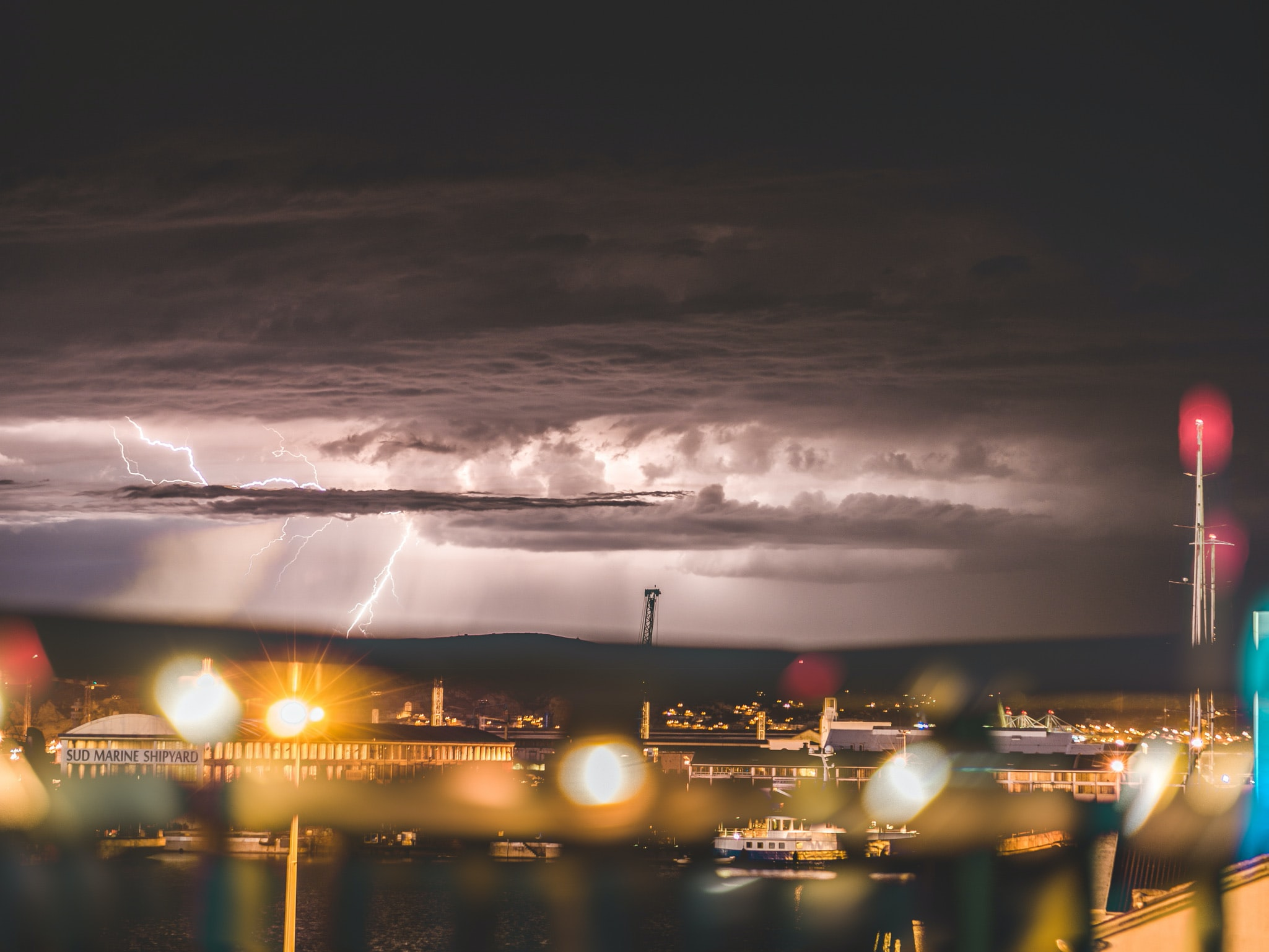 high angle photography of buildings under gray sky with lighting strikes