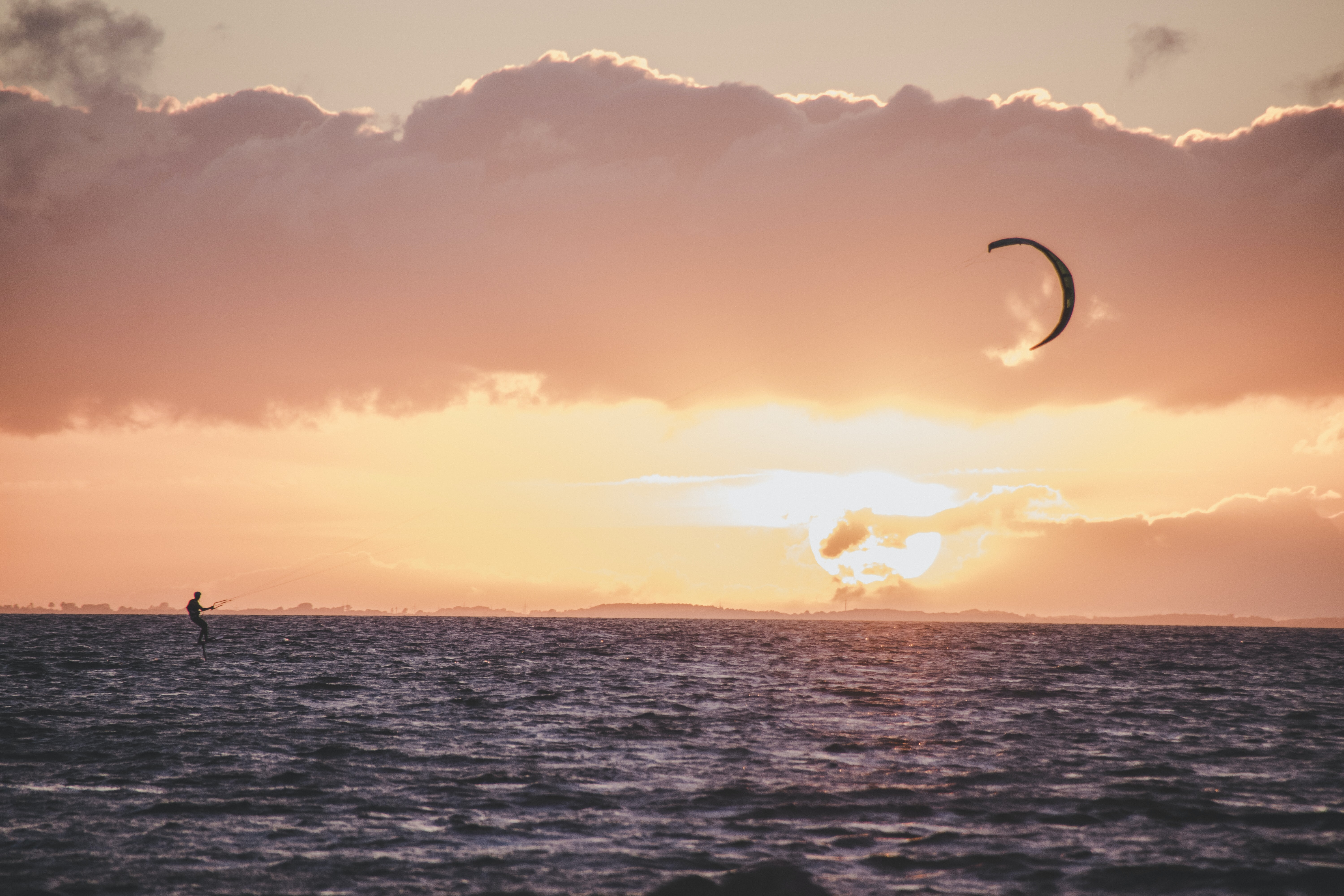 person in water ski on body of water during sunset